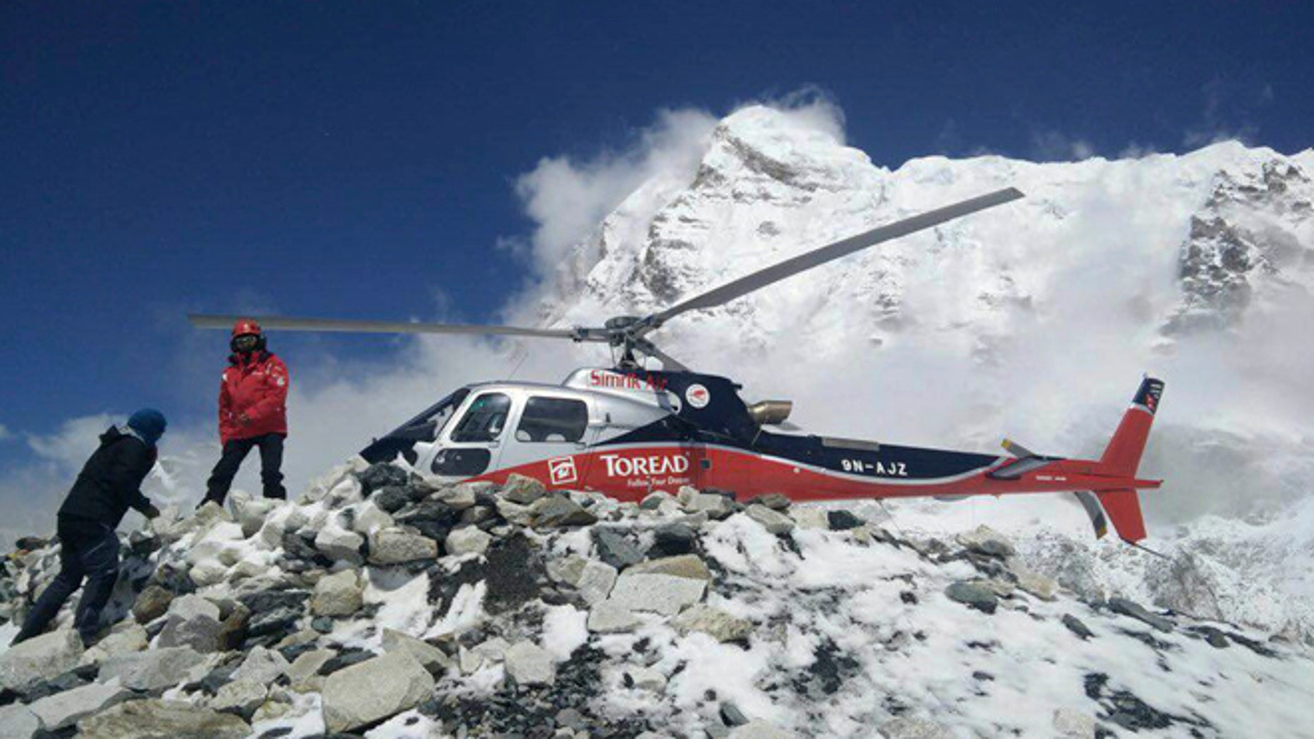 A helicopter prepares to rescue people from camp 1 and 2 at Everest Base Camp, Nepal. On Monday, State Department officials confirmed the death of two Americans at the base camp from a large avalanche triggered by Nepal's massive earthquake. (Azim Afif via AP)