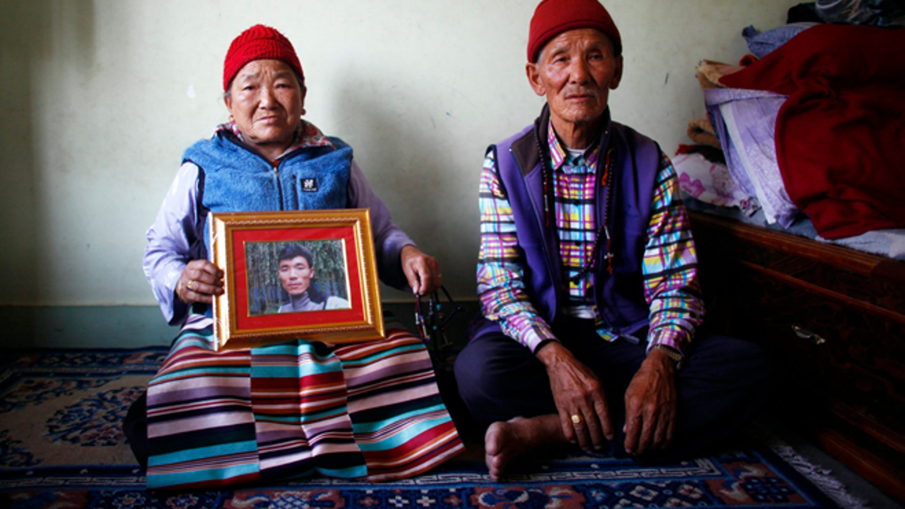 April 23, 2014: Nimdige Sherpa holds a portrait of her son Ang Kaji Sherpa, killed in an avalanche on Mount Everest, with her husband Ankchu Sherpa seated beside her in their rented apartment in Katmandu, Nepal.  (AP)