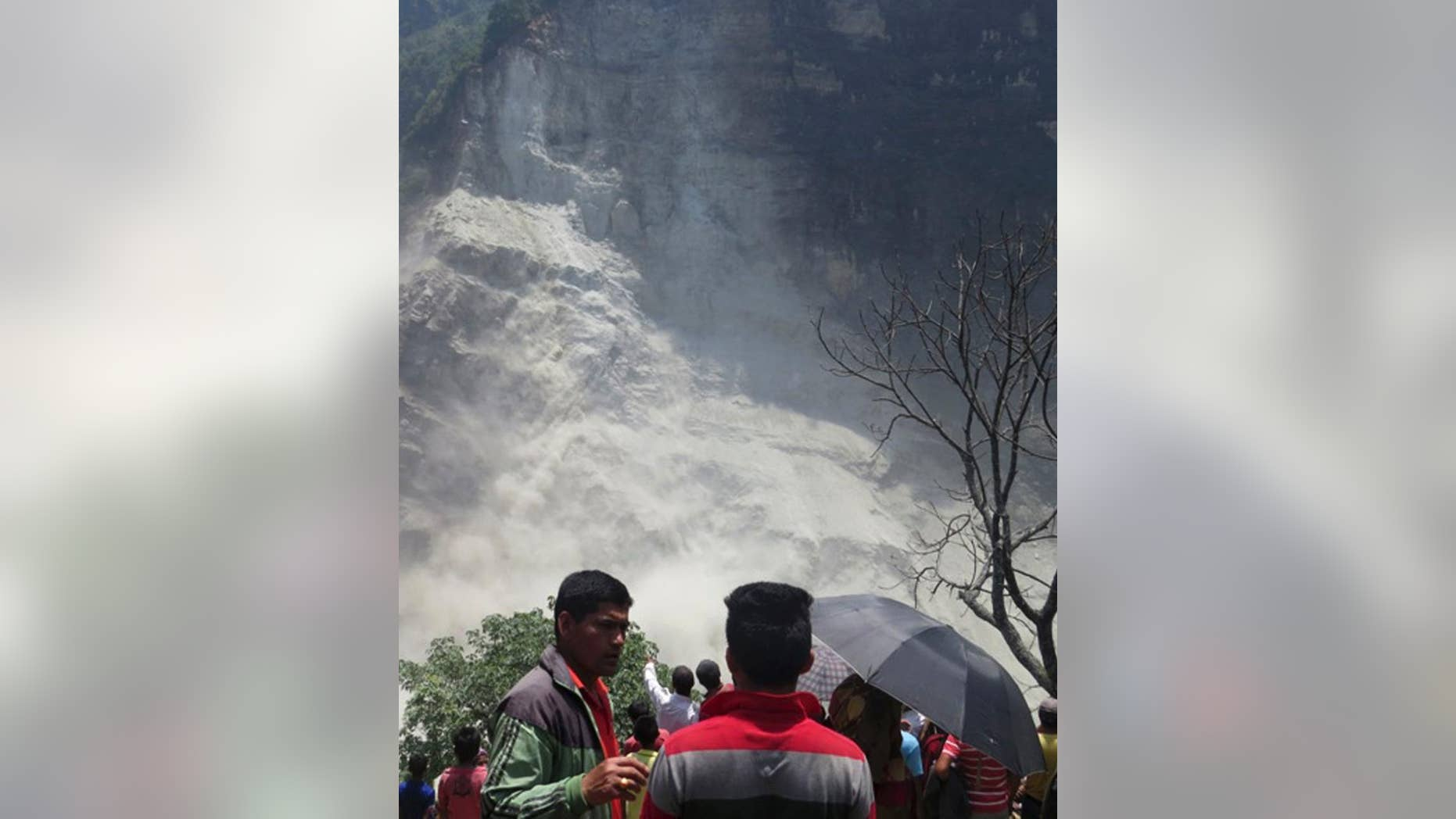 People gather at the site of a landslide north of Beni Bazaar, Nepal, Sunday, May 24, 2015. Thousands of people fled villages and towns along a mountain river in northwest Nepal on Sunday after it was blocked by a landslide that could burst and cause flash floods, officials said. (AP Photo/M.B. Astha)
