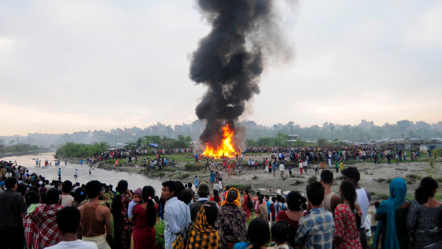 Nepalese gather around the burning wreckage at the crash site of a Sita Air airplane near Katmandu, Nepal, early Friday, Sept. 28, 2012. The plane carrying trekkers into the Everest region crashed Friday morning in Nepal's capital, and all 19 people on board are believed dead, authorities said. Thirteen people on board were foreigners, while three passengers and the three crew members were from Nepal, said Katmandu airport chief Narayan Bastakoti. (AP Photo)