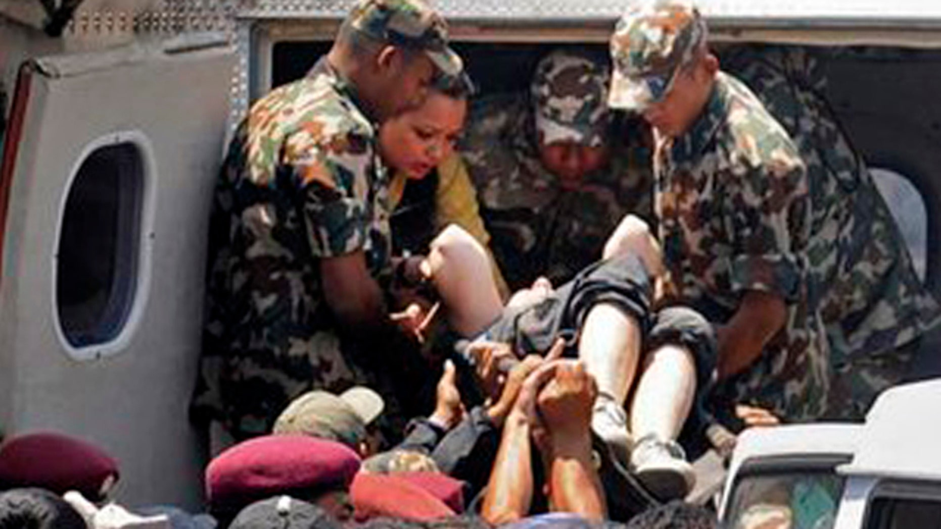 May 14, 2012: Nepalese army soldiers carry a survivor of a plane crash flown for treatment to the nearby city of Pokhara, Nepal.