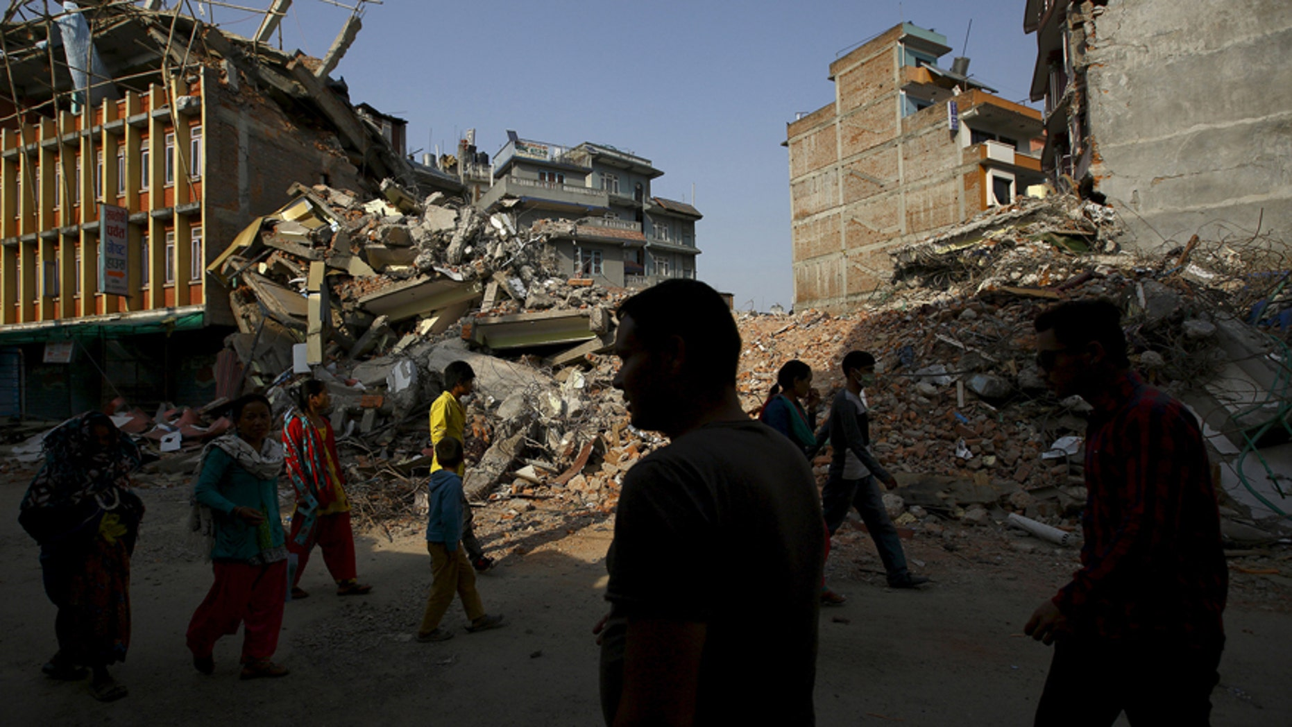 Nepalese people walk along a street near the debris of collapsed houses, a month after the April 25 earthquake in Kathmandu, Nepal May 25, 2015.