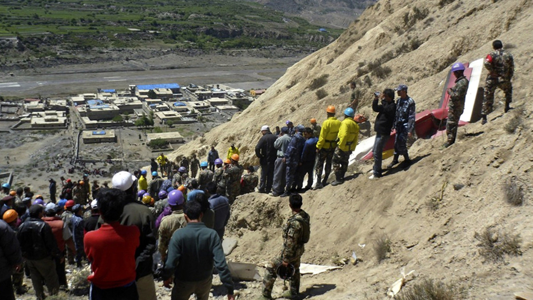 May 14: Nepalese rescue workers and officials inspect the site of a plane crash near Jomsom, 125 miles northwest of the capital, Katmandu.