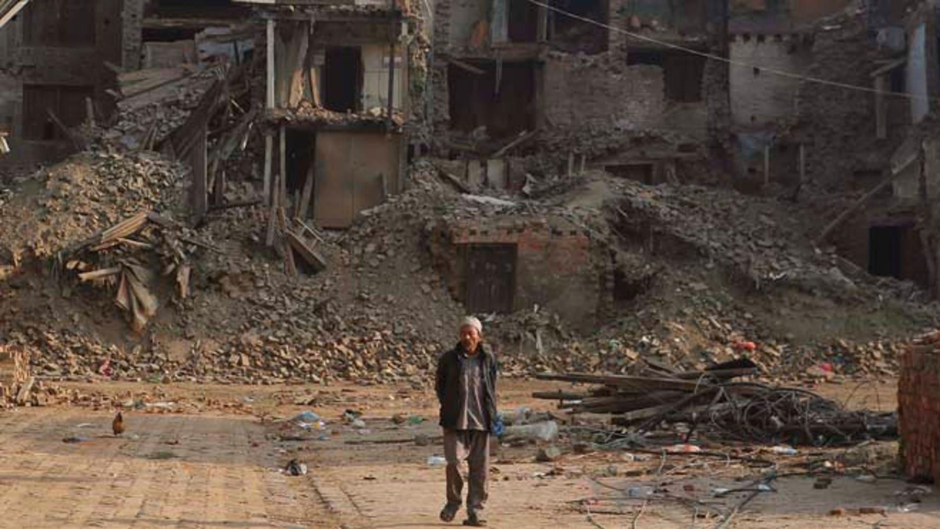 May 25, 2015: A Nepalese man walks past damaged houses one month after the deadly 7.8 magnitude earthquake in Kathmandu, Nepal.
