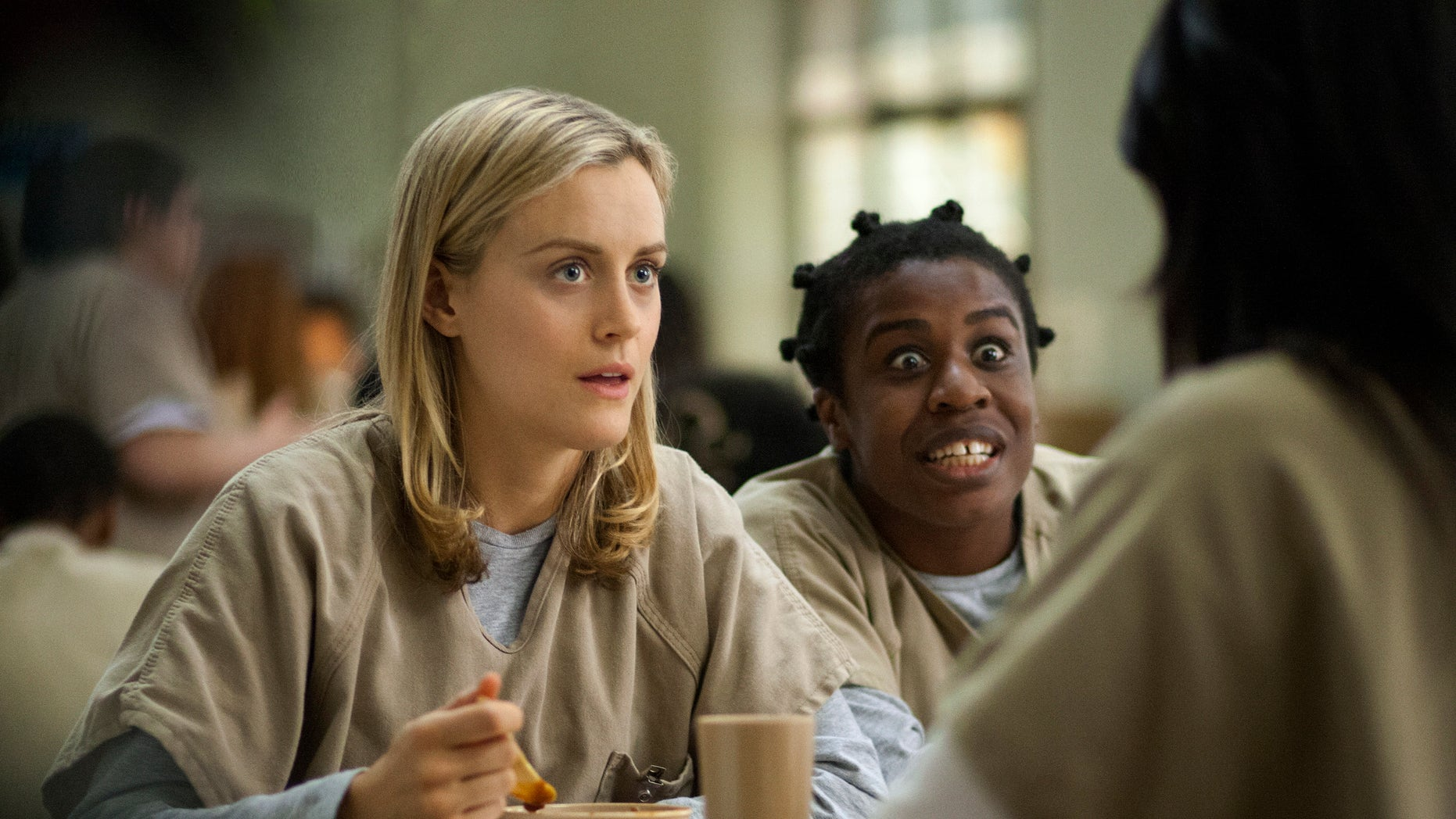 This image released by Netflix shows Taylor Schilling, left, and Uzo Aduba in a scene from 'Orange Is the New Black.'