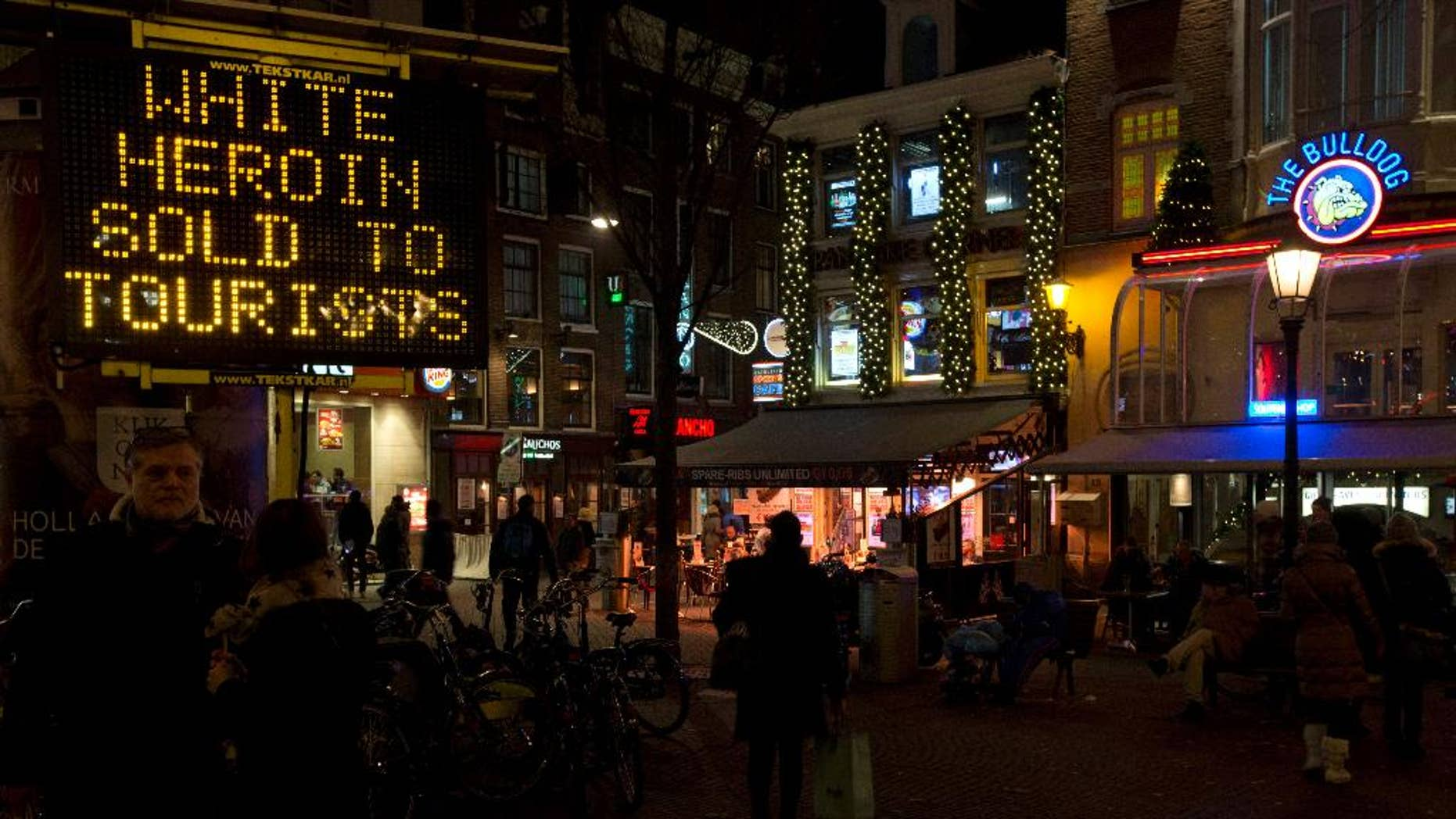"""FILE - In this Dec. 5, 2014 file photo an electronic sign outside Amsterdam's famous Bulldog coffee shop, right, warns tourists of """"white heroin"""", an extremely dangerous drug which is being sold as cocaine to tourists in Amsterdam. Police in Amsterdam said Tuesday April 7, 2015, that a 42-year-old man who turned himself in on Saturday could be a dealer who sold white heroin to tourists, telling them that it was cocaine, three tourists have died in recent months and 20 other became unwell after taking heroin. (AP Photo/Peter Dejong, File)"""