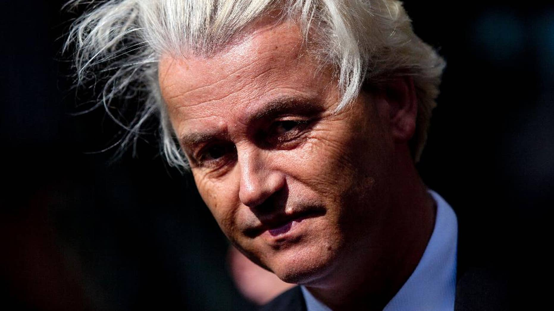 """FILE - In this May 12, 2014 file photo Dutch lawmaker Geert Wilders pauses, as he speaks to journalists outside the Dutch National Bank in Amsterdam. Dutch authorities on Thursday, Dec. 18, 2014, said they will prosecute Wilders for hate speech over a chant in which he asked his supporters whether they wanted more or fewer Moroccans in the Netherlands and they shouted back """"Fewer! Fewer! Fewer!"""" The announcement marks the second time Wilders has faced charges linked to his anti-immigrant and anti-Islam rhetoric. He was acquitted of similar charges in 2011 for comparing Islam with Naziism and calling for a ban on the Quran. (AP Photo/Peter Dejong, File)"""