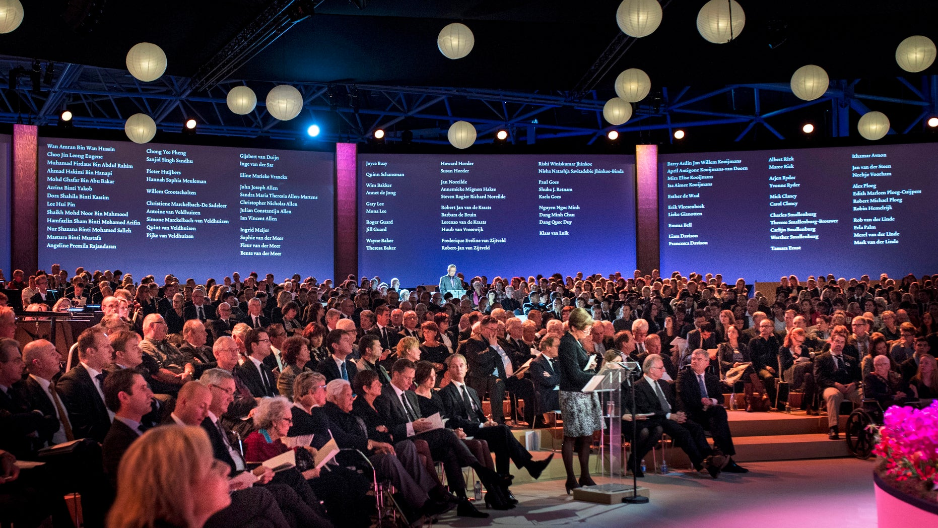 Nov. 10, 2014 - A relative reads out names of victims in front of screens listing those who died, during a commemoration ceremony at RAI in Amsterdam, Netherlands, for loved ones of victims of the Malaysia Airlines Flight 17 disaster. Hundreds gathered for the ceremony, nearly 4 months after the passenger jet was downed over eastern Ukraine killing all 298 people on board.