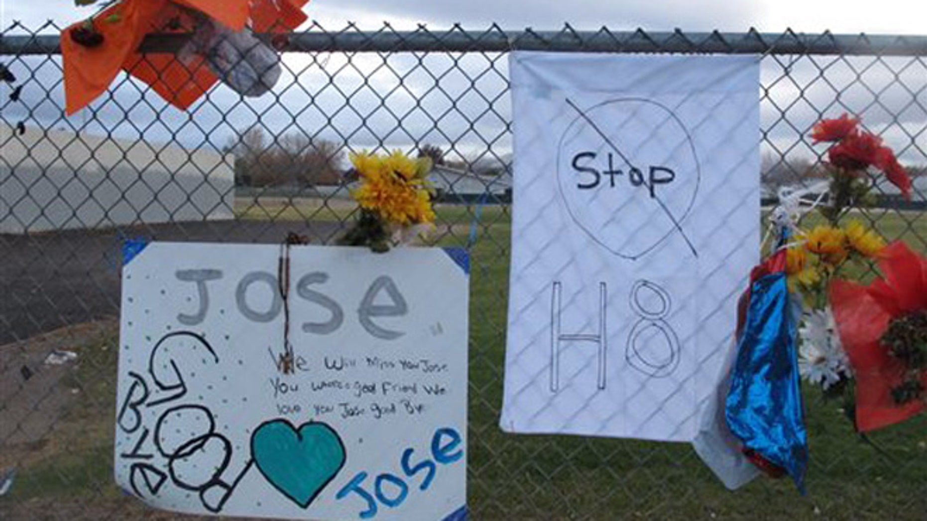 Friends have added a message to Jose Reyes and a small wooden cross at a memorial pictured Monday, Oct. 28, 2013, outside Sparks Middle School, where the seventh-grader fatally shot a teacher and wounded two 12-year-old classmates before killing himself in the school yard a week ago. Students returned to classes Monday for the first time since the Oct. 21 shooting. (AP Photo/By Scott Sonner)