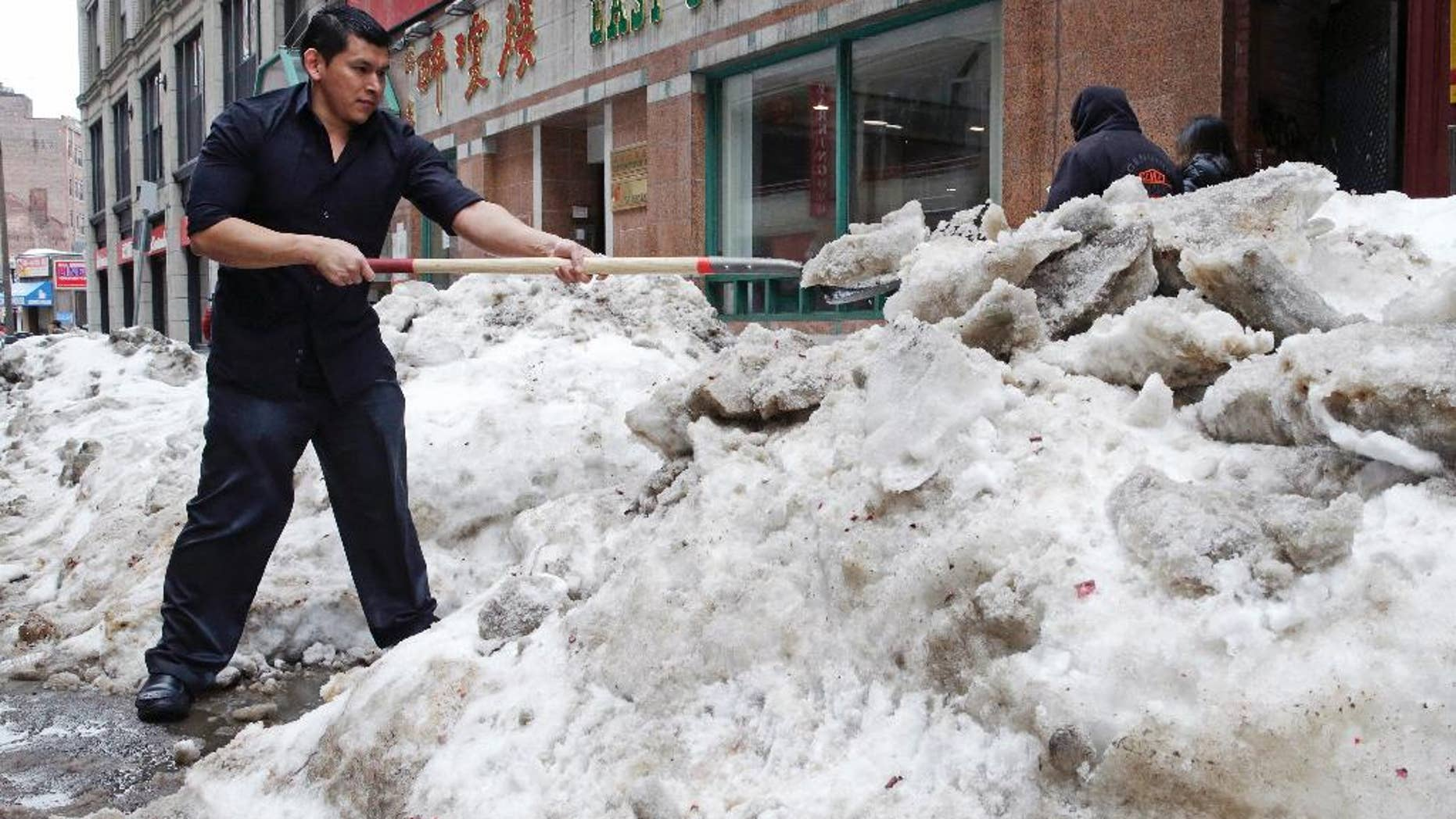 FILE - In this March 4, 2015 file photo, waiter Melvin Angel shovels snow outside the restaurant he works at in the Chinatown neighborhood of Boston.  Every work day lost during New England's historic winter has meant millions of dollars out of the regional economy. Retailers and restaurants were among the hardest hit, but hotels, transportation companies and other tourism businesses struggled too. (AP Photo/Charles Krupa)