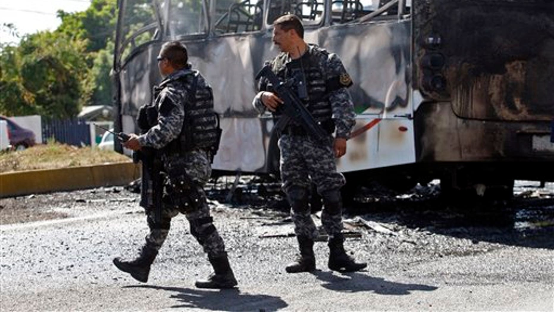 State police stand next to a charred passenger bus, that was extinguished by firefighters in Guadalajara, Mexico, Friday, May 1, 2015.