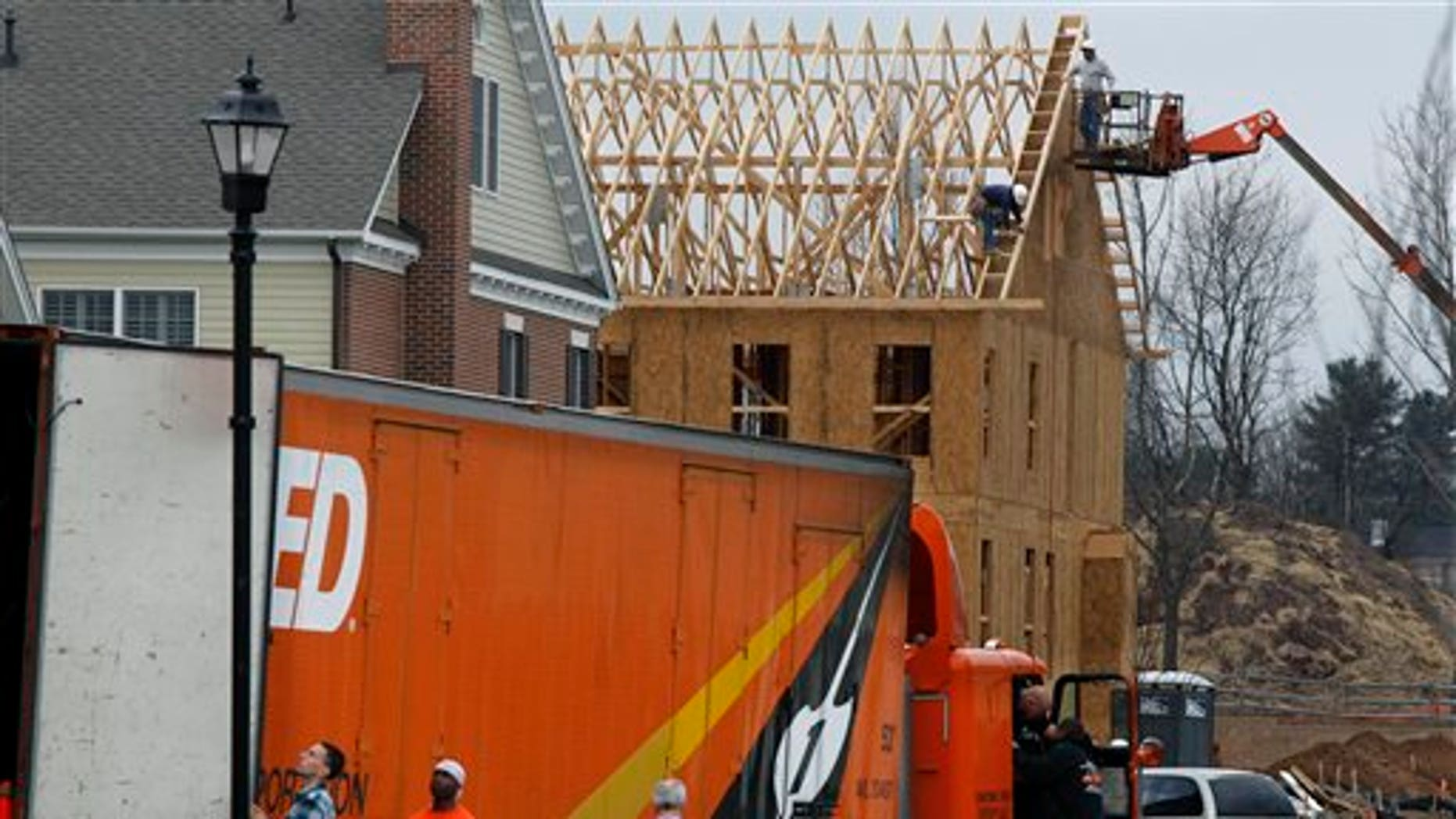 April 7: Construction continues on a new home in Newtown, Pa., as a moving van delivers furniture at a nearby finished home.