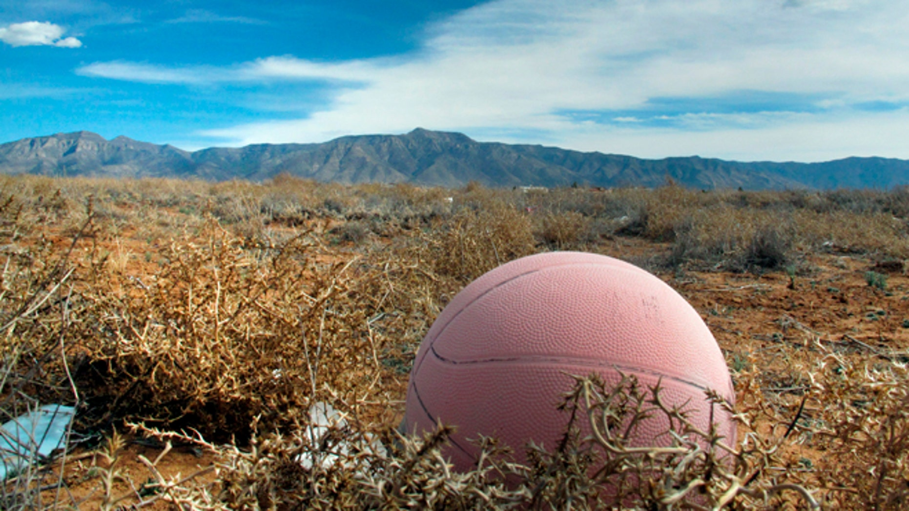 An old basketball in an abandon lot south of Albuquerque is shown where authorities say the body of a 12-year-old boy was discovered, Wednesday, Feb. 19, 2014, in Meadow Lake, N.M. Valencia County Sheriff Louis Burkhard said Alex Madrid of Albuquerque was found in the field Tuesday after his parents reported him missing. (AP Photo/Russell Contreras)