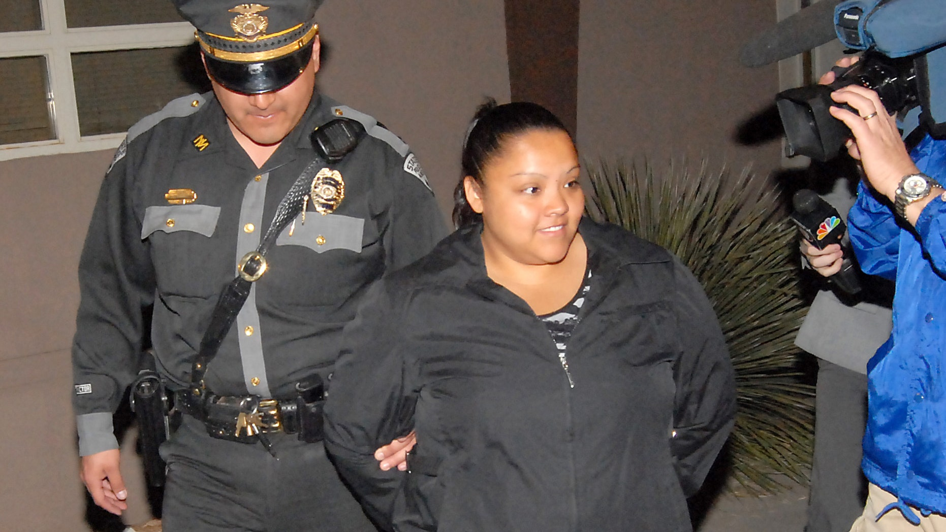 Priscilla Morales, secretary for former Sunland Park city councilor Dario Hernandez, is handcuffed and escorted into a police car by New Mexico State Police officer Raul Robles on Tuesday just as polls were closing in Sunland Park, N.M. Morales is the fourth arrest in conection with alleged voter fraud. (AP PHOTO/Las Cruces Sun-News, Robin Zielinski)