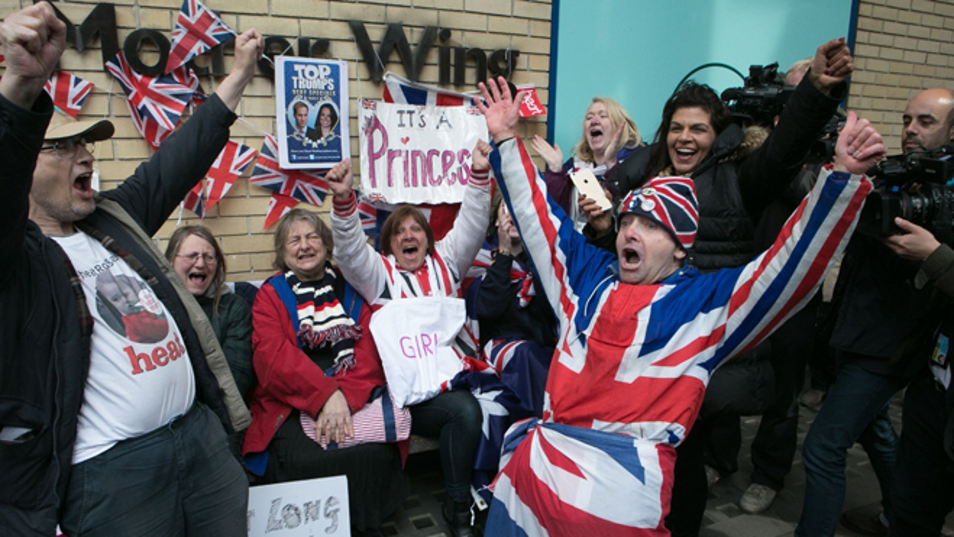 """Royal fans and well wishers react after Kensington Palace announced that Kate, the Duchess of Cambridge, had given birth to a girl, outside the Lindo Wing of St. Mary's Hospital, London, Saturday, May 2, 2015. Kensington Palace said in a brief statement that Prince William's wife """"was safely delivered of a daughter"""" at 8:34 a.m. London time (0734 GMT), less than three hours after she was admitted to central London's St. Mary's Hospital. (Daniel Leal-Olivas/PA via AP) UNITED KINGDOM OUT, NO SALES, NO ARCHIVE"""