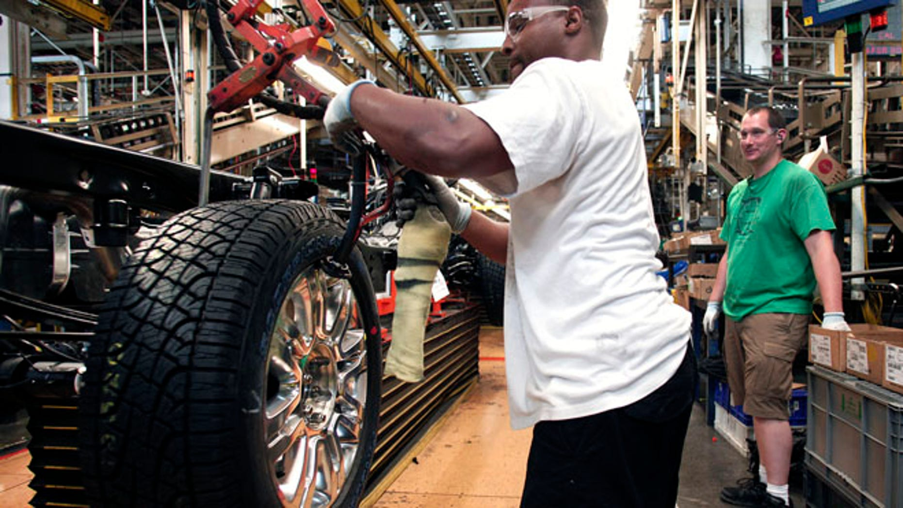 DEARBORN, MI - JUNE 13: New Ford worker Reginald Gilder, in his first week on the job, performs a tire installation on a new 2014 Ford F-150 truck as it undergoes assembly at the Ford Dearborn Truck Plant June 13, 2014 in Dearborn, Michigan. Production for the 2015 model F-150 at the plant is expected to begin in the 4th quarter of this year. (Photo by Bill Pugliano/Getty Images)
