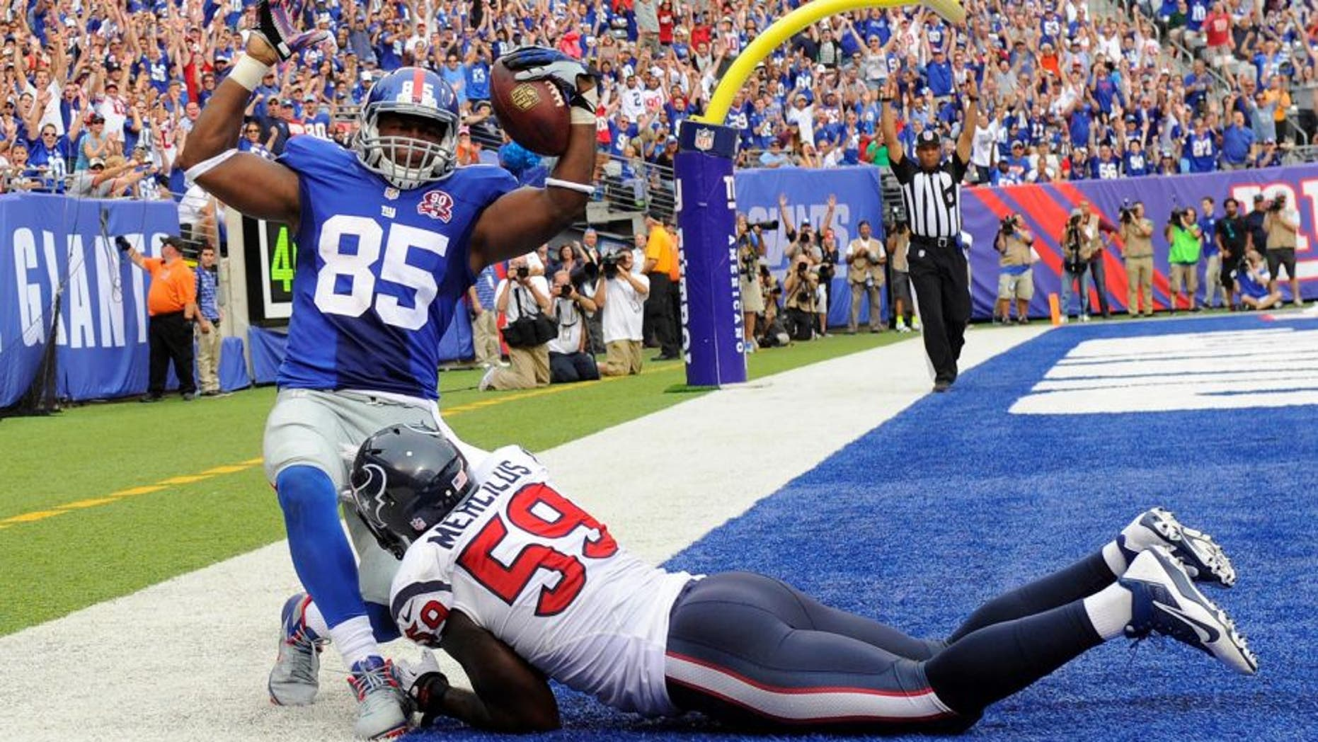 Sep 21, 2014; East Rutherford, NJ, USA; New York Giants tight end Daniel Fells (85) scores a touchdown against Houston Texans outside linebacker Whitney Mercilus (59) at MetLife Stadium. Mandatory Credit: Robert Deutsch-USA TODAY Sports