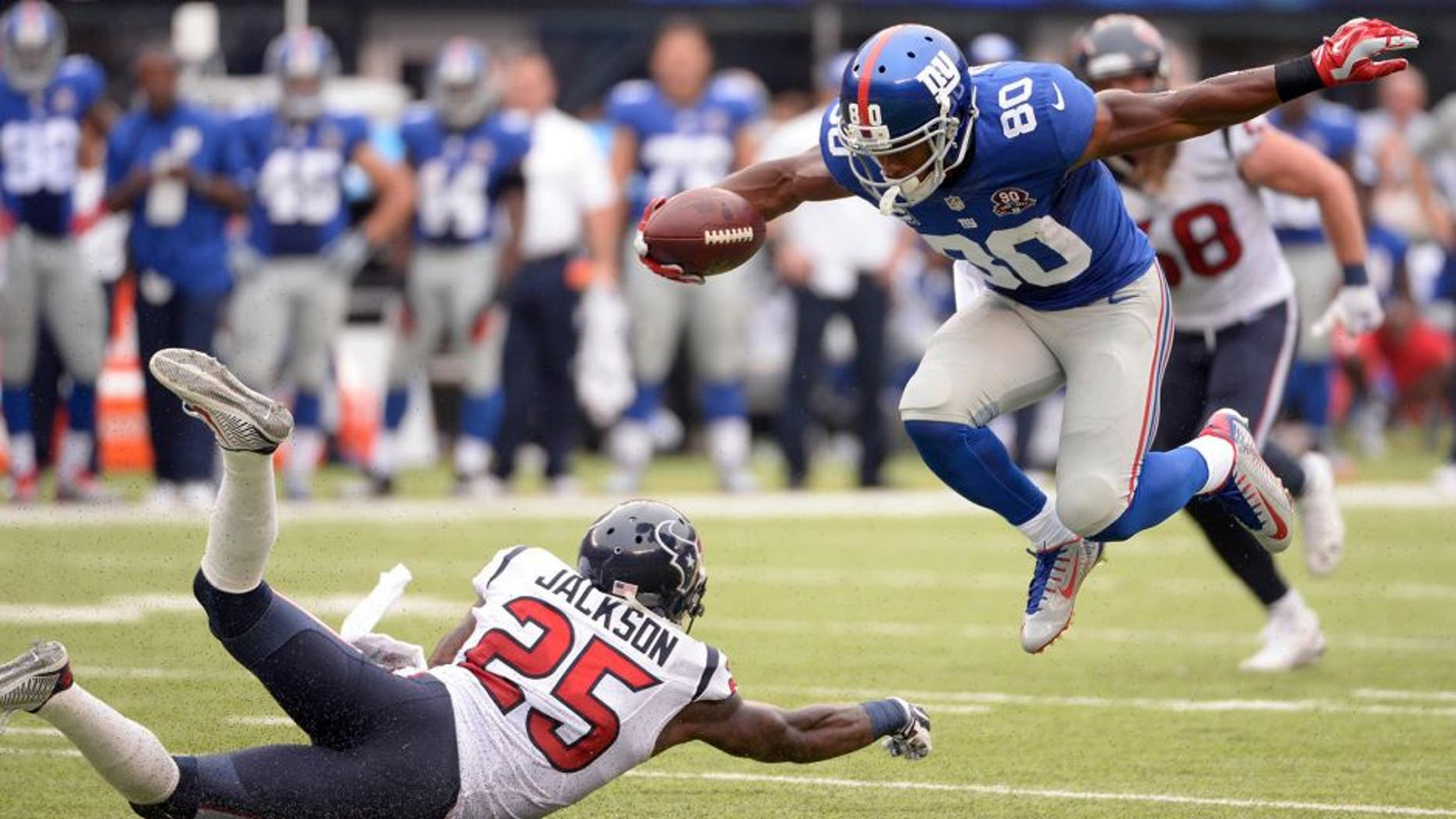 Sep 21, 2014; East Rutherford, NJ, USA; New York Giants wide receiver Victor Cruz (80) scores a touchdown past Houston Texans cornerback Kareem Jackson (25) at MetLife Stadium. Mandatory Credit: Robert Deutsch-USA TODAY Sports