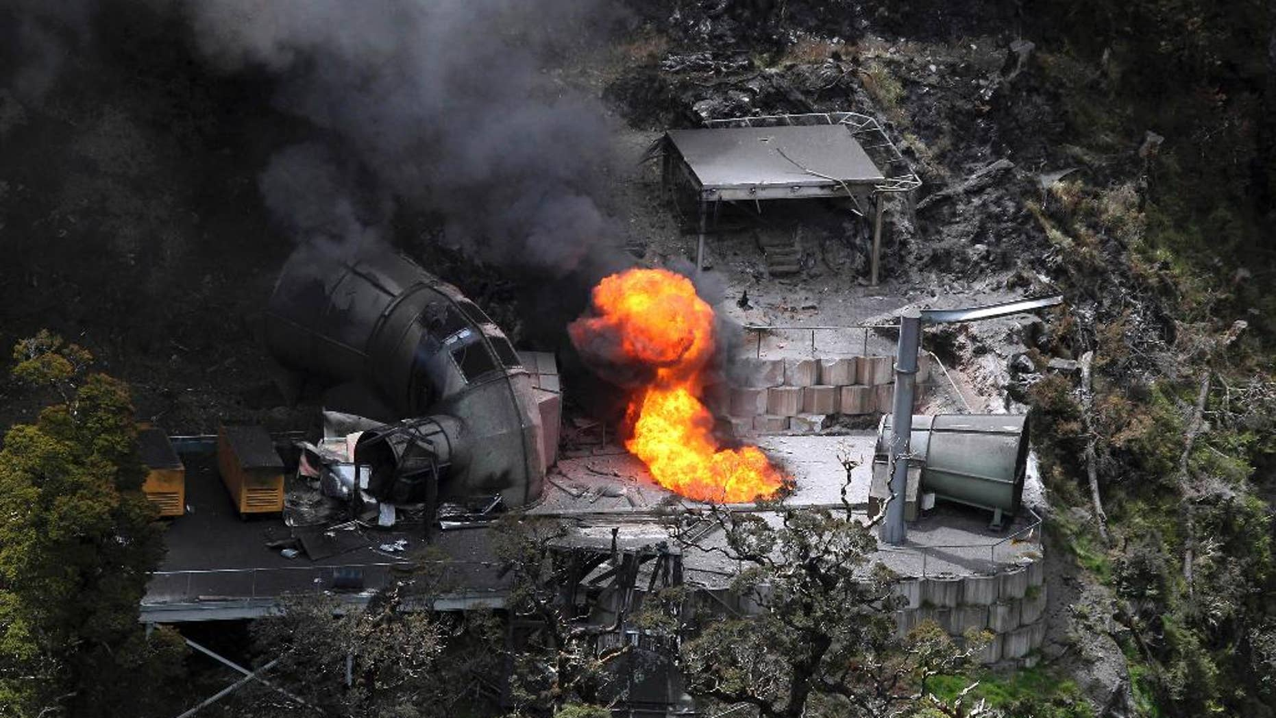 FILE - In this Nov. 30, 2010 file photo, flames burn from a ventilation shaft above the Pike River mine which has fatally trapped 29 miners and contractors in Greymouth, New Zealand. The owners of a New Zealand coal mine where the bodies of 29 workers remain entombed after a methane-fueled explosion four years ago said Thursday, Nov. 6, 2014 they won't go back into the mine because it remains too dangerous. (AP Photo/NZPA, Iain McGregor, File)  NEW ZEALAND OUT