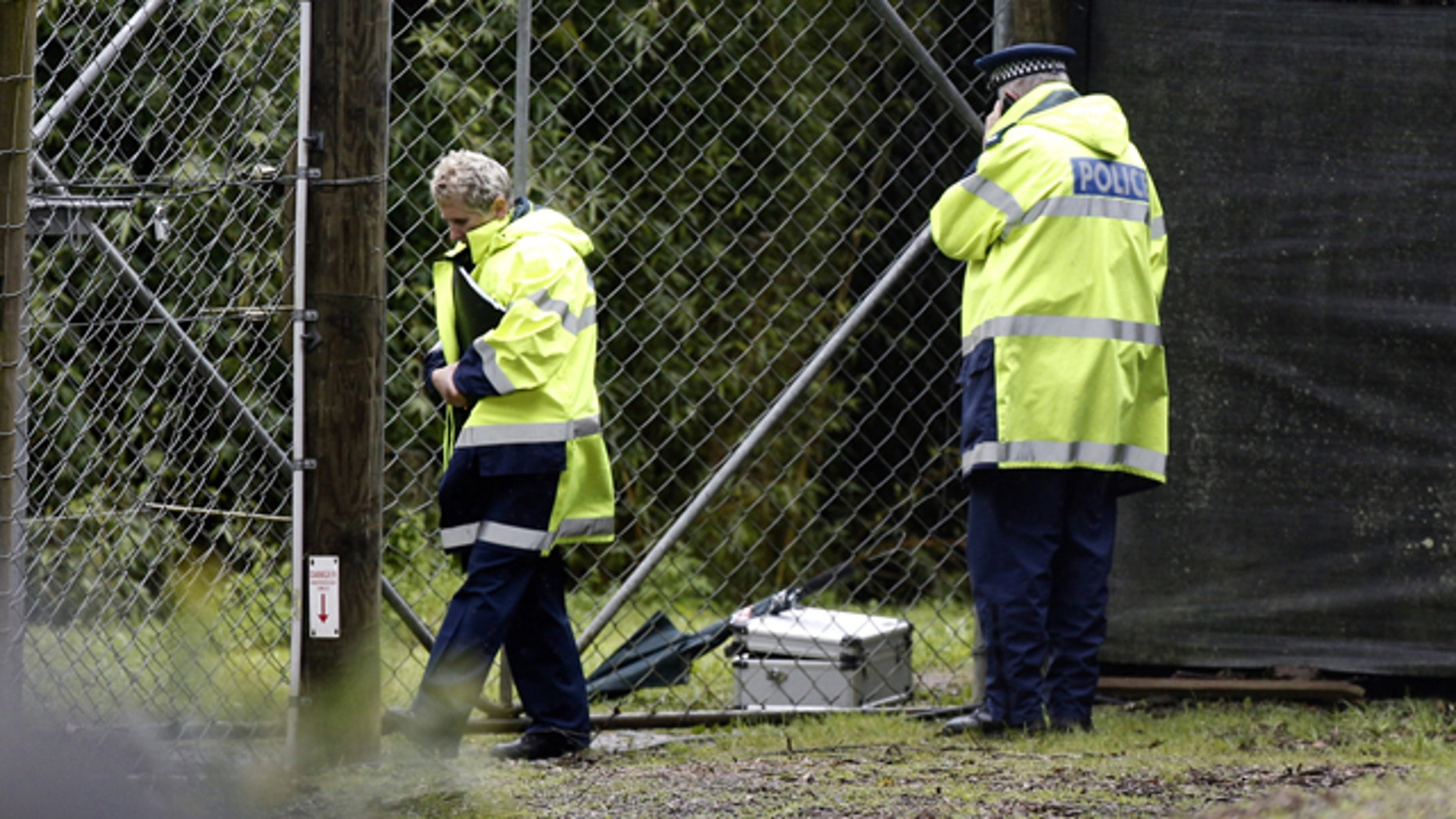 Sept. 20, 2015: Police stand at the shut gates at the Hamilton (New Zealand) Zoo after a female zookeeper was killed by one of its tigers. Police said the woman died at the scene, and asked the zoo to order all visitors to leave and close its doors until Thursday. (Nick Reed/New Zealand Herald via AP).