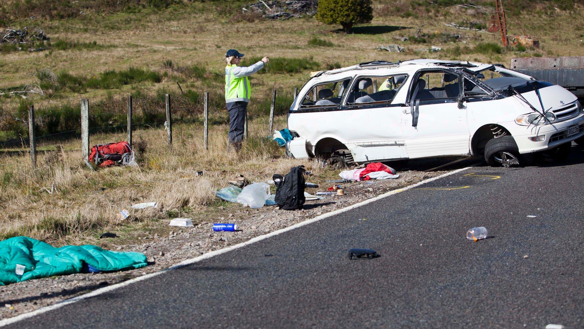 May 12, 2012: Policemen examine the scene of a minivan crash near Turangi, New Zealand, Saturday.