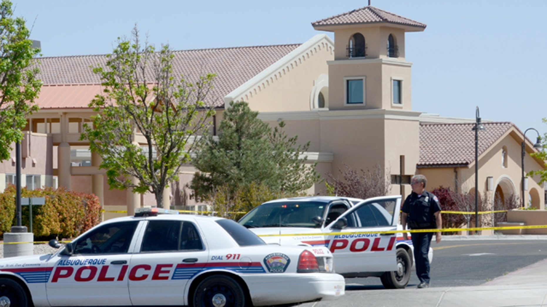 April 28, 2013: An Albuquerque Police officer walks behind the tape at St. Jude Thaddeus Catholic Church.