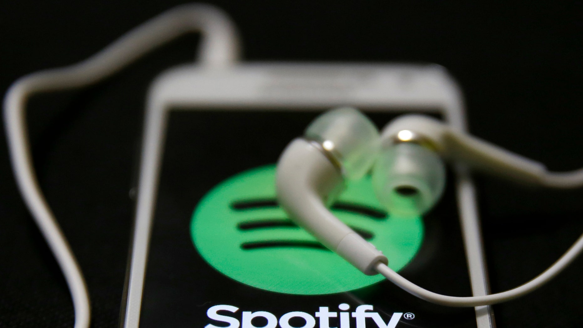 Earphones are seen on top of a smart phone with a Spotify logo on it, in Zenica February 20, 2014. Online music streaming service Spotify is recruiting a U.S. financial reporting specialist, adding to speculation that the Swedish start-up is preparing for a share listing, which one banker said could value the firm at as much as $8 billion (4 billion pounds). REUTERS/Dado Ruvic (BOSNIA AND HERZEGOVINA - Tags: SCIENCE TECHNOLOGY BUSINESS SOCIETY) - RTX1971J