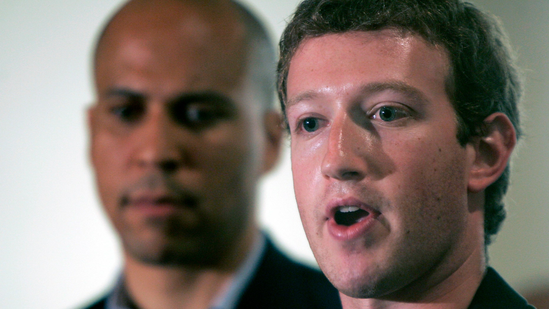 FILE - In this Sept. 25, 2010 file photo, Mark Zuckerberg, right, founder and CEO of Facebook talks about his donation of $100 million to help Newark public schools during a news conference in Newark, N.J. With Zuckerberg is Newark mayor Cory Booker and N.J. Gov. Chris Christie, not in picture.   More than three years after Zuckerberg committed $100 million toward remaking Newark's struggling schools, the district is engulfed in a dispute over proposed large-scale teacher layoffs that is threatening to derail wider reform efforts.   (AP Photo/Rich Schultz)