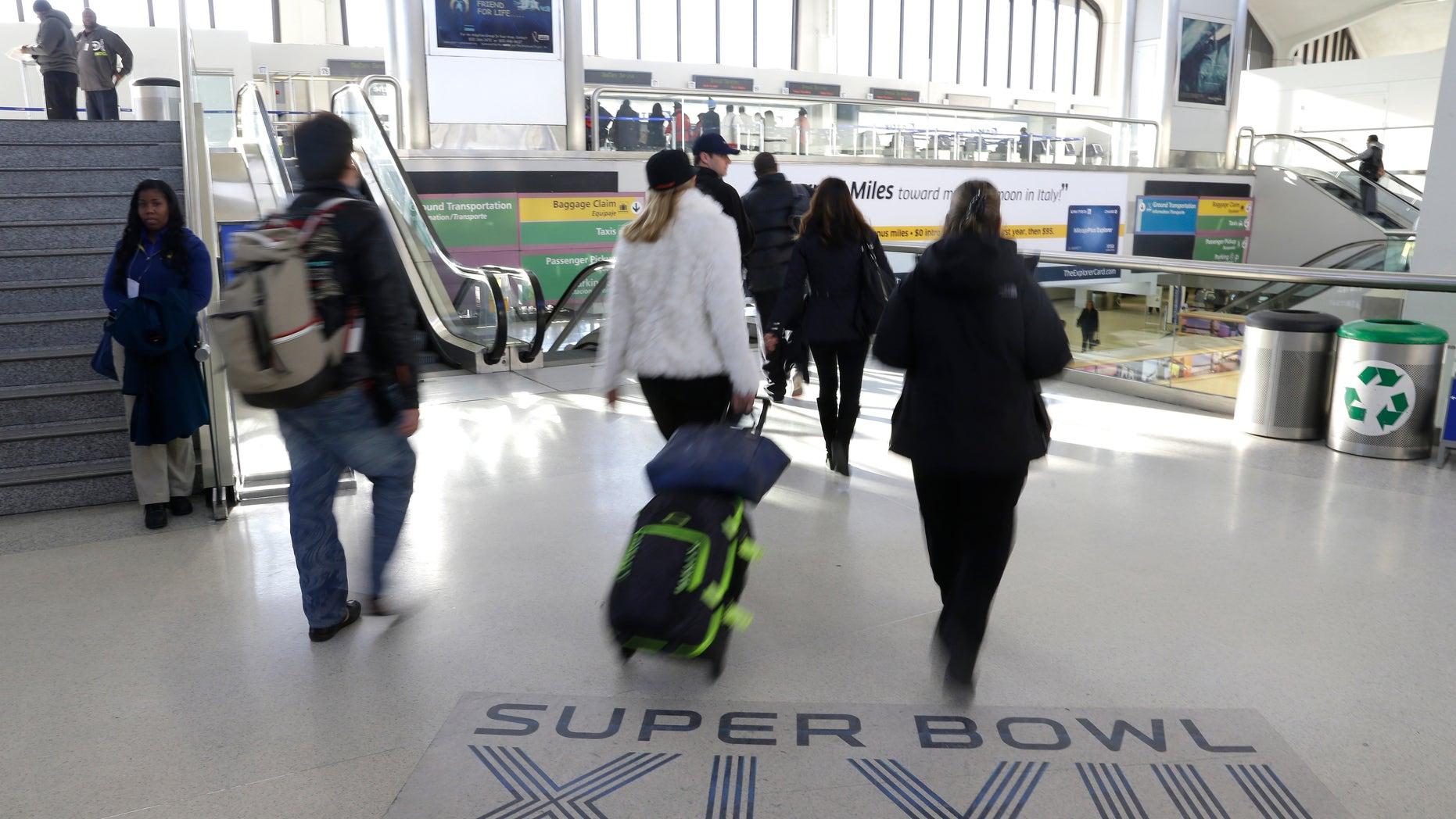 Jan. 30 2014: Arriving passengers walk past a Super Bowl sign at Newark Liberty International Airport in Newark, N.J.