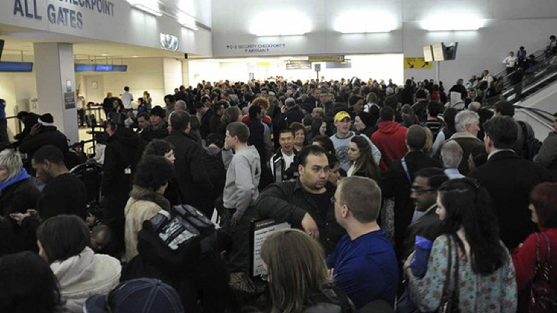 Passengers wait to be re-screened in front of the security checkpoint at Terminal C at Newark International Airport in Newark, New Jersey January 3, 2010. (Reuters)