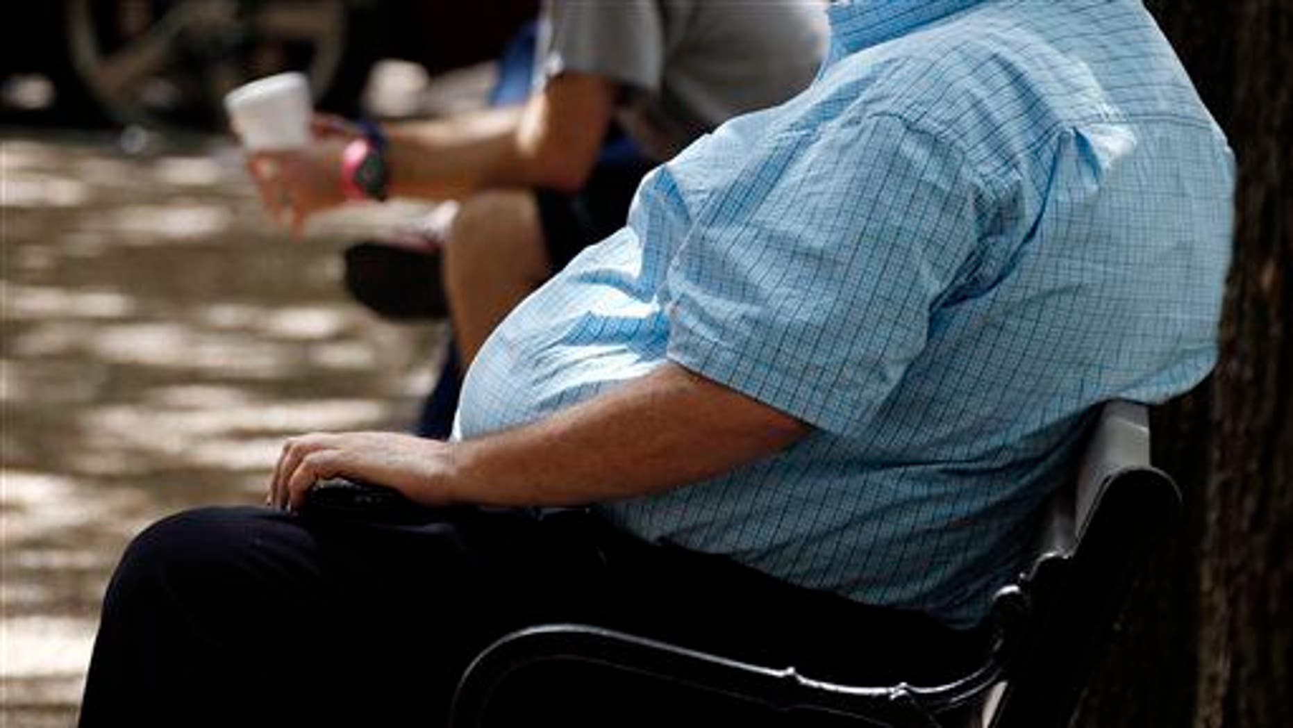 A heavyset man rests on a bench in Jackson, Miss., Sept. 4, 2014.