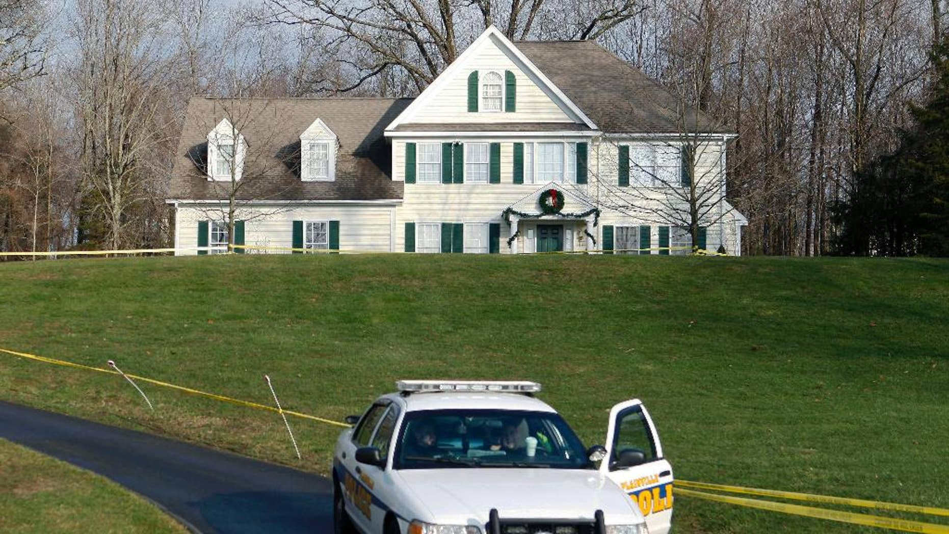 FILE - In this Dec. 18, 2012 file photo a police cruiser sits in the driveway of the home of Nancy Lanza, in Newtown, Conn. The Colonial-style home where Newtown school shooter Adam Lanza lived with his mother has been transferred to the town in a deal with a bank. Nancy Lanza was killed there by her son before he forced his way into Sandy Hook Elementary School, Dec. 14, 2012, in Newtown, where he killed 20 first-graders and six educators. The future use of the house and property will be decided later. (AP Photo/Jason DeCrow, File)