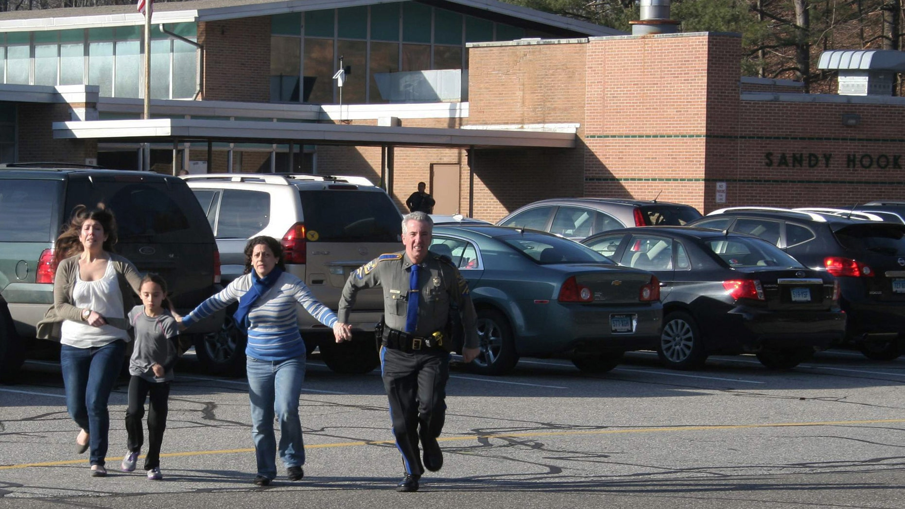 FILE - In this Friday, Dec. 14, 2012, file photo provided by the Newtown Bee, a police officer leads two women and a child from Sandy Hook Elementary School in Newtown, Conn., where a gunman opened fire, killing 26 people, including 20 children. A prosecutor is planning to release a report on the investigation into the massacre at Sandy Hook Elementary School on Monday, Nov. 25, 2013, but the public will have to wait longer for the Connecticut state policeâs full accounting of the crime.(AP Photo/Newtown Bee, Shannon Hicks, File) MANDATORY CREDIT: NEWTOWN BEE, SHANNON HICKS