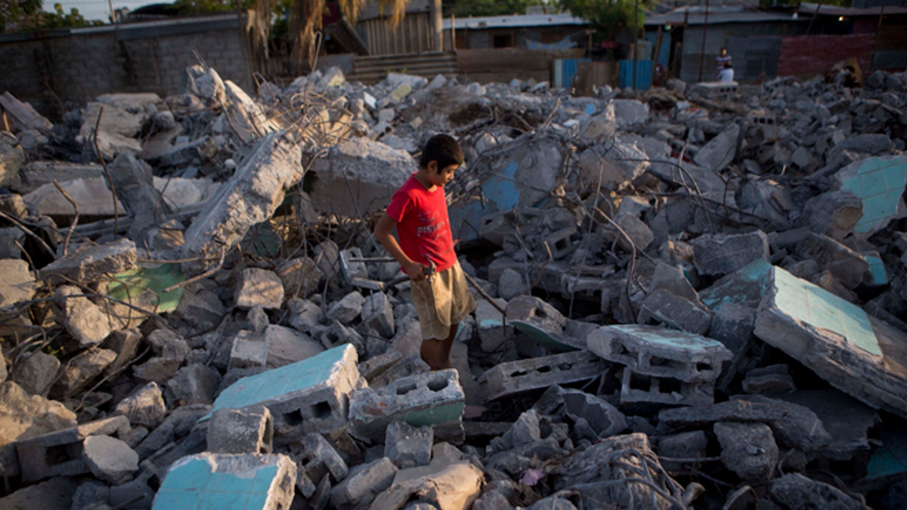A boy searches for metal to sell, in the rubble of a building that was damaged in a 1972 earthquake and demolished after several recent earthquakes in Managua, Nicaragua, Monday, April 14, 2014. People who had been living in earthquake damaged buildings were ordered to evacuate after several quakes have affected Nicaragua since Thursday. (AP Photo/Esteban Felix)