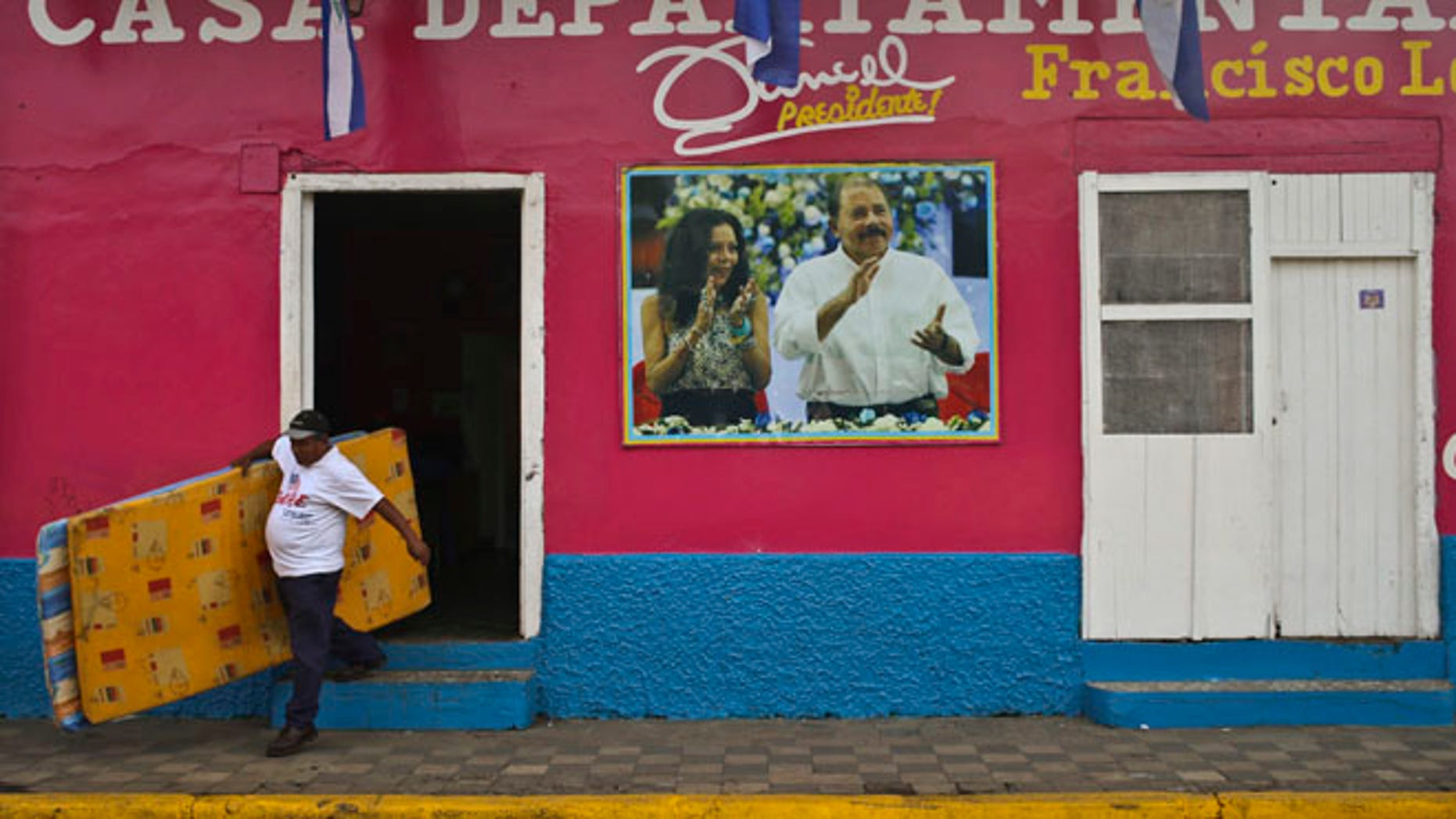 A man leaves the Sandinista National Front Party headquarters, in Masaya, Nicaragua, Saturday, Nov. 5, 2016. Nicaraguan President Daniel Ortega, pictured on the facade of the headquarters with his running mate and wife, Rosario Murillo, appears to have a clear path to a third consecutive term following recent moves that weakened the countryââ¬â¢s opposition. (AP Photo/Esteban Felix)