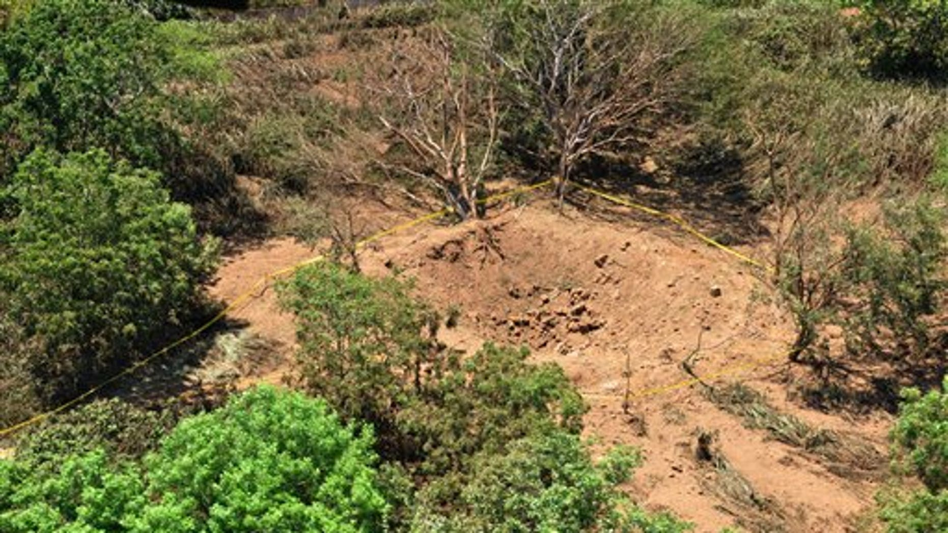 """In this Sunday Sept. 7, 2014, publicly distributed handout photo provided by the Nicaraguan Army shows an impact crater made by a small meteorite in a wooded area near Managua's international airport and an air force base. Nicaraguan government spokeswoman Rosario Murillo said Sunday that a loud boom heard overnight by residents of the capital was a """"relatively small"""" meteorite that """"appears to have come off an asteroid that was passing close to Earth.""""  (AP Photo/Nicaraguan Army)"""