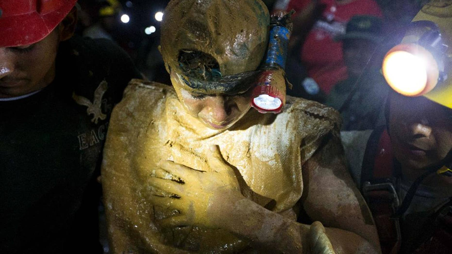 A rescued miner looks down as he leaves the El Comal gold and silver mine after being rescued in Bonanza, Nicaragua, Friday, Aug. 29, 2014.  The first 11 of 24 freelance gold miners trapped by a collapse in a mine have been rescued and crews were working early Saturday to free more, officials said. (AP Photo/Esteban Felix)