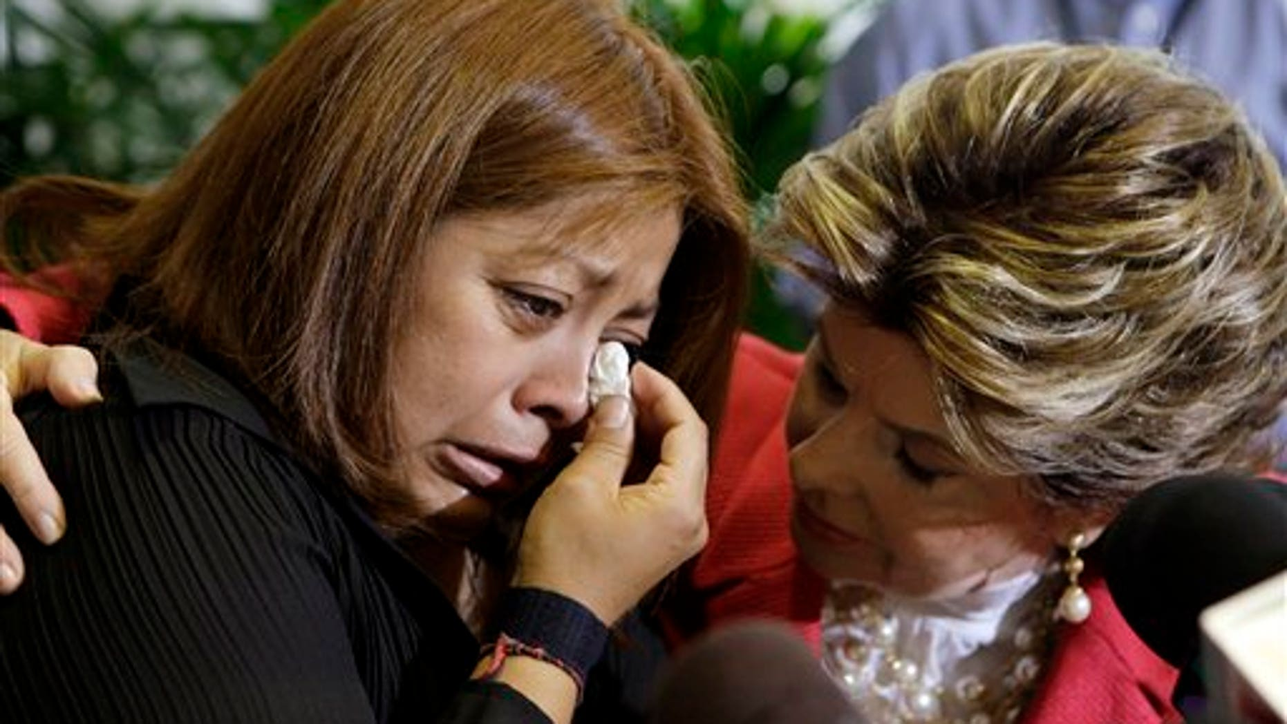 Nicky Diaz, left, former housekeeper for California GOP gubernatorial candidate Meg Whitman, weeps as she talks to reporters with attorney Gloria Allred in Los Angeles Wednesday, Sept. 29, 2010.  Diaz alleges that Whitman was notified seven years ago that the worker might be in the country illegally, but did nothing about it.  (AP Photo/Reed Saxon)