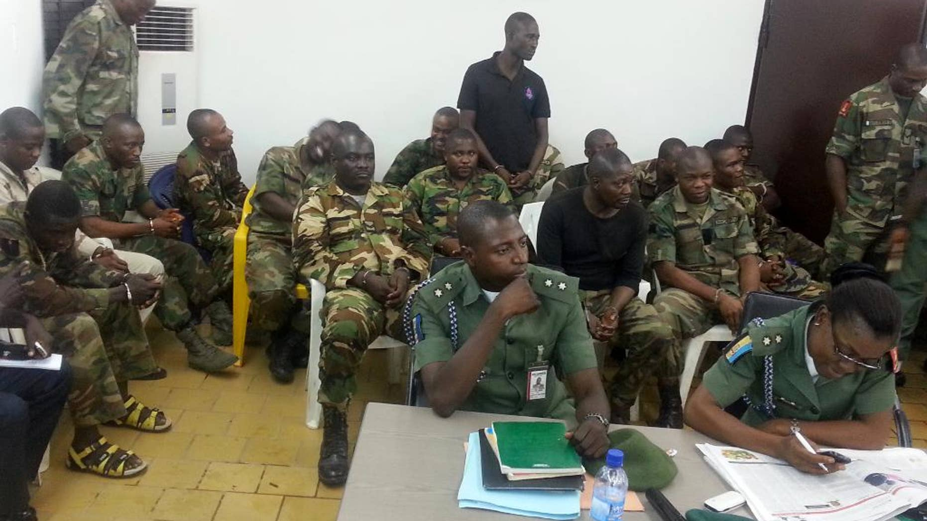 In this photo taken with a mobile phone Tuesday, Sept. 16. 2014 in Abuja Nigeria. Unidentified military prosecutors sit in the front row, while soldiers accused of an attack on their commander appear before a court martial in Abuja. Twelve soldiers fighting an Islamic insurgency in northeast Nigeria have been sentenced to death by firing squad for mutiny and attempted murder of their commanding officer. In a decision read early Tuesday by Brig. Gen. Chukwuemeka Okonkwo, the military tribunal found 12 soldiers guilty and five others innocent. One was sentenced to 28 days in jail with hard labor. ( AP Photo)