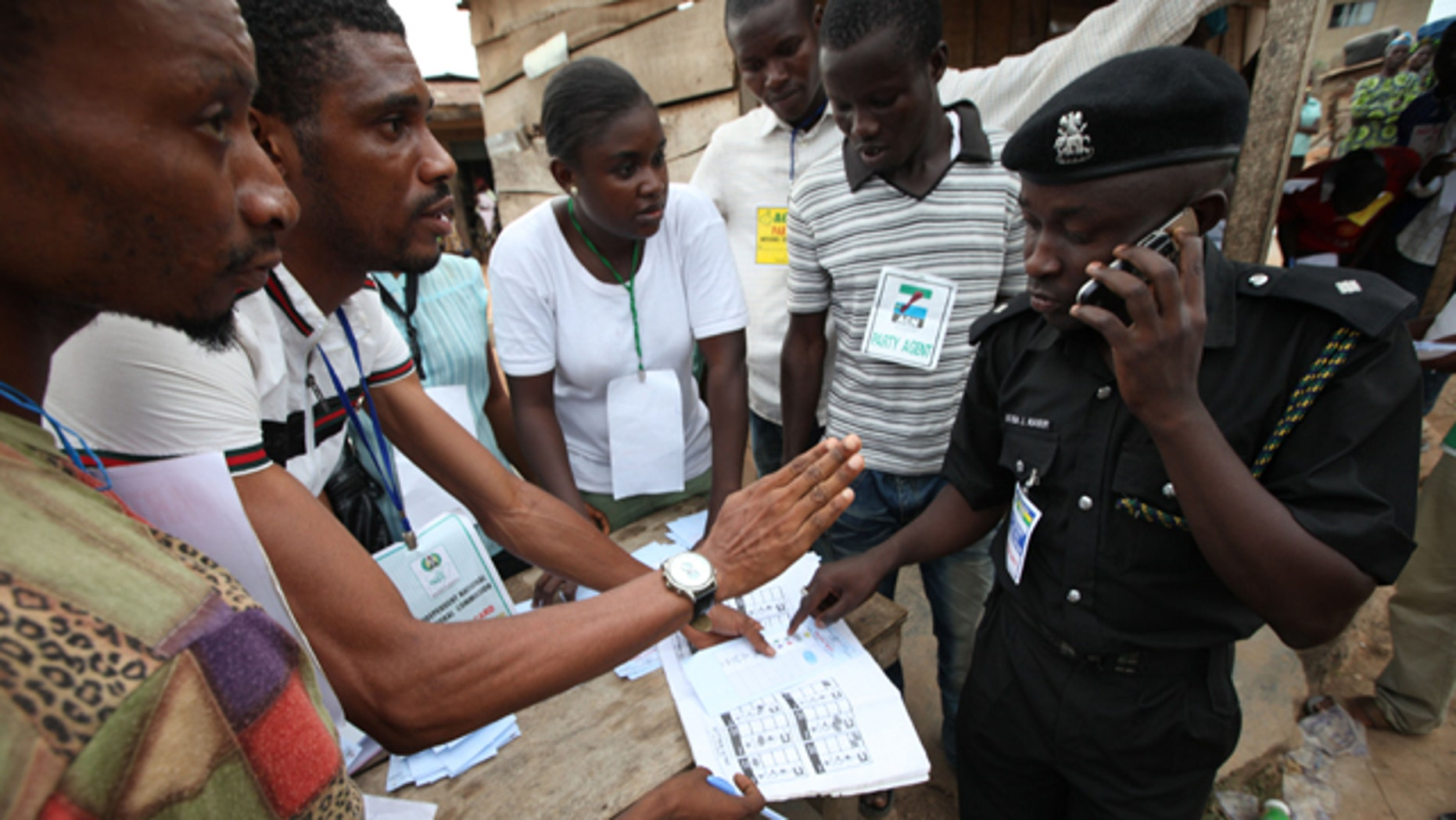 A Police officer, right, checks election results from electoral officers after the National Assembly election in Ibadan, Nigeria,Saturday, April 9, 2011. Nigeria's voters put their inked fingers to ballots Saturday for the first round in the nation's crucial April election, coming out to vote despite bomb attacks and communal violence. Poll workers shoved themselves into rickety commercial buses, cars and other vehicles to travel to the roughly 120,000 polling stations spread throughout Africa's most populous nation. Voting for the nation's estimated 73.5 million voters largely began at noon across the country. (AP Photo/Sunday Alamba)
