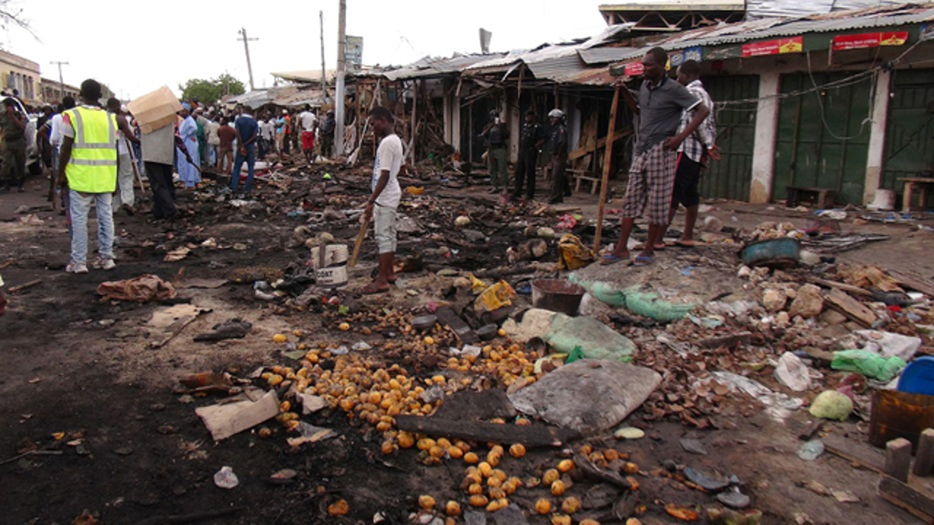 July 2, 2014: People gather at the scene of a car bomb explosion at the central market in Maiduguri, Nigeria. ( AP Photo/Jossy Ola)
