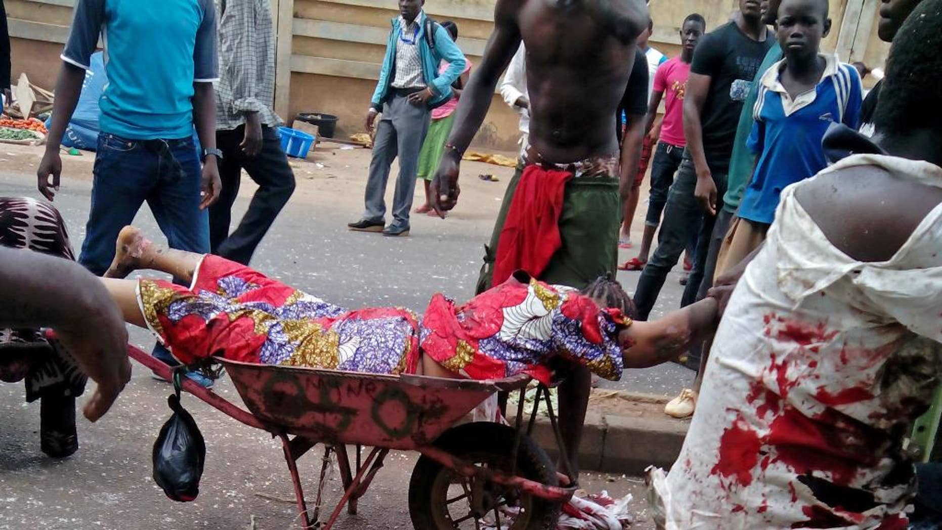 EDITORS NOTE GRAPHIC CONTENT  An injured woman is carried after bombs exploded at a bus terminal and market in Jos, Nigeria, Tuesday, May 20, 2014. Two car bombs exploded at a bustling bus terminal and market in Nigeria's central city of Jos on Tuesday, and witnesses said dozens of people were killed. No one immediately claimed responsibility for the twin car bombs, but they bore the hallmarks of Boko Haram, an Islamic extremist group. (AP Photo/Stefanos Foundation)