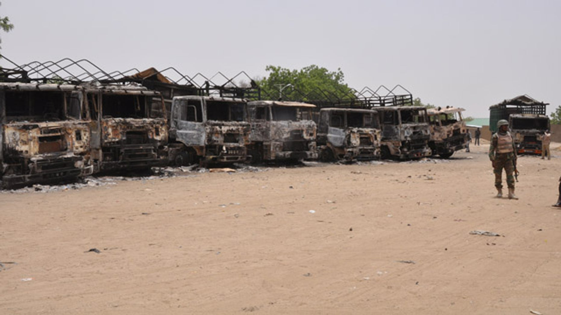May 11, 2014: A soldier stands guard in front of burnt trucks following an attack by Islamic militants in Gambaru, Nigeria.  (AP Photo/Jossy Ola)
