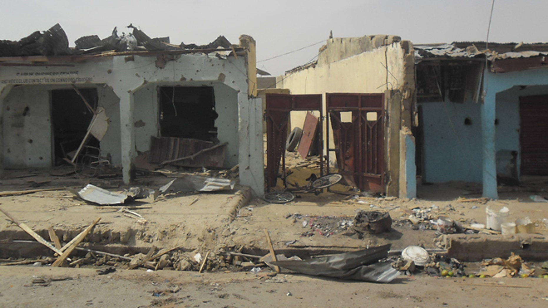 June 18, 2014: Bloodstains seen on the street and damage buildings following a suicide bomb explosion at a World cup viewing center in Damaturu, Nigeria. There was no immediate claim for the blast but Boko Haram was suspected.
