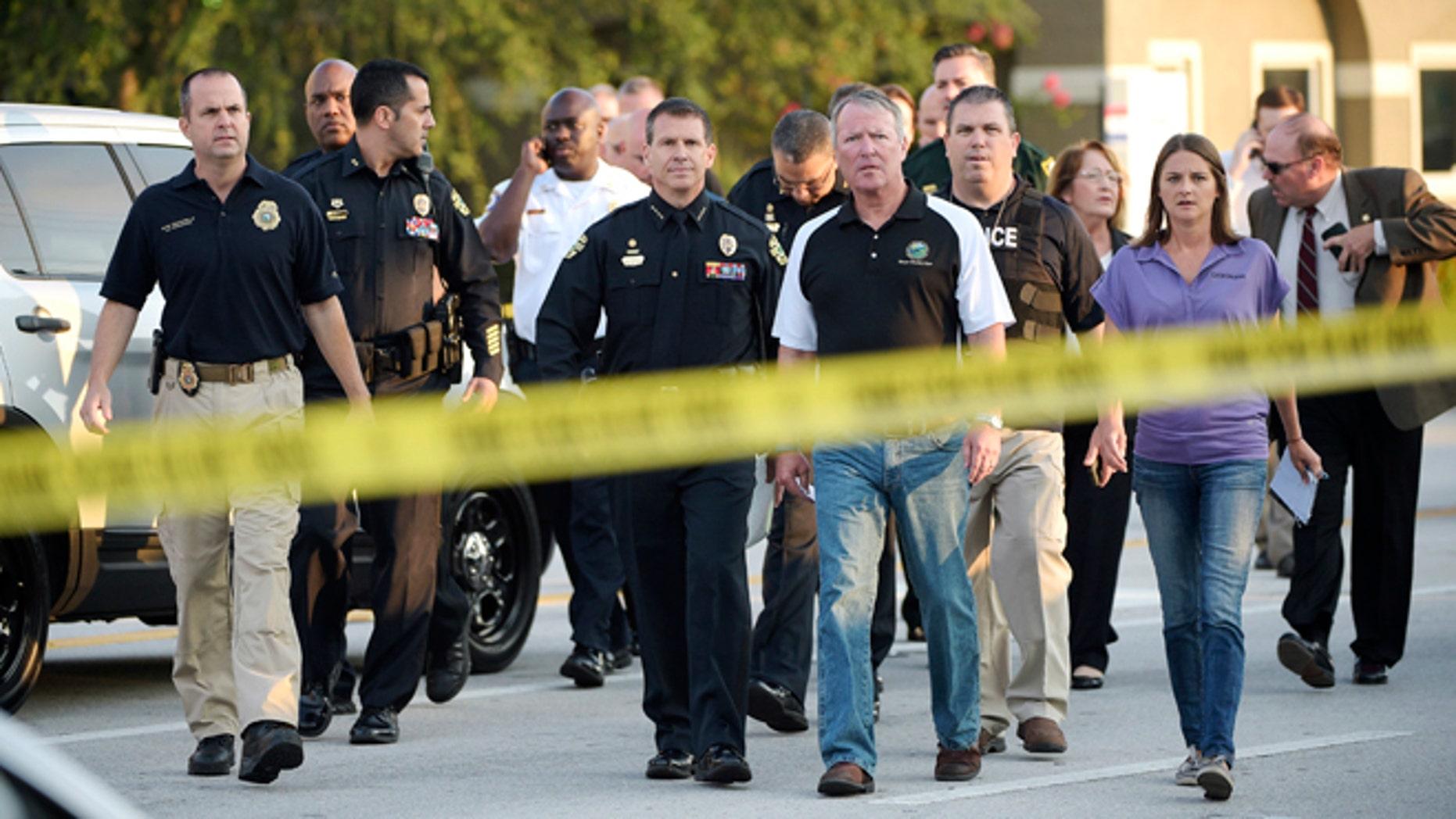 Orlando Mayor Buddy Dyer, center right, and Orlando Police Chief John Mina, center left, arrive to a news conference after a fatal shooting at Pulse Orlando nightclub in Orlando, Fla., Sunday, June 12, 2016. (AP Photo/Phelan M. Ebenhack)