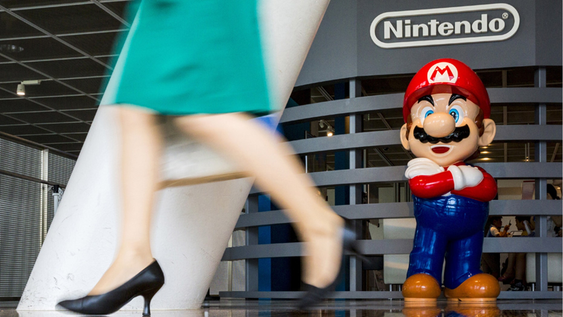 "A woman walks past a figure of 'Mario', a character in Nintendo's ""Mario Bros."" video games, at a Nintendo centre in Tokyo July 29, 2015."