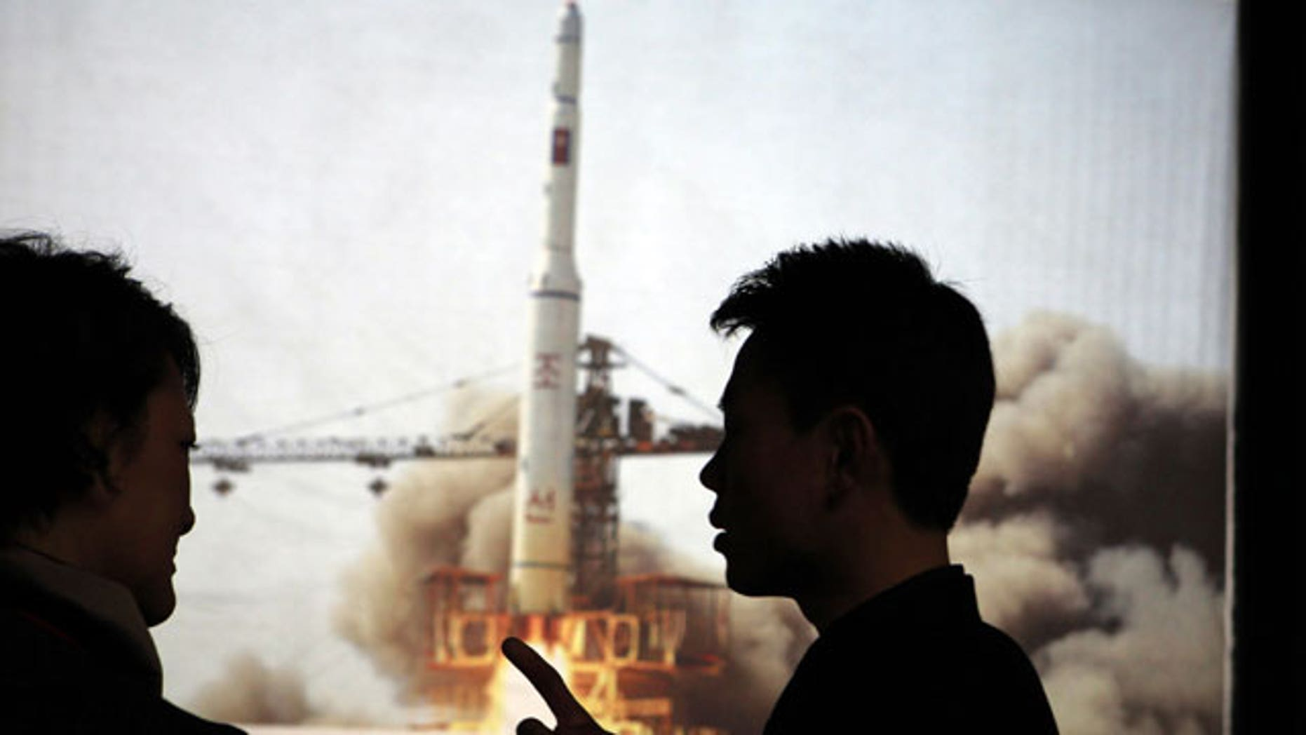 In this photo taken Tuesday, April 10, 2012, North Korean guide Kim Won Ho, right, speaks to a foreign journalist near a photo depicting the 2009 satellite rocket launch at the Three Revolutions exhibition hall in Pyongyang, North Korea.