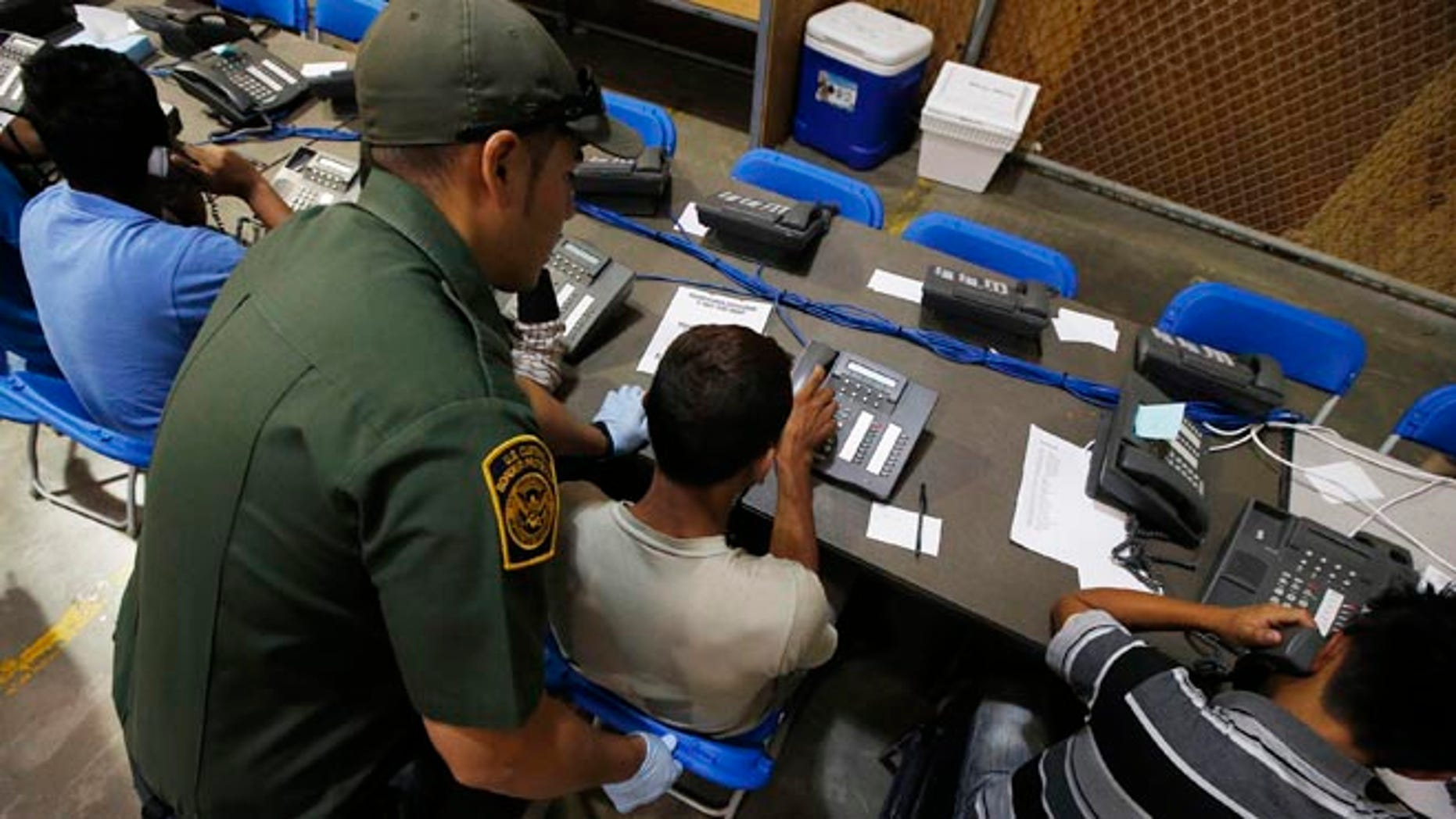 FILE: June 18, 2014: A Customs and Border Protection officer helps youths make calls, at the agency's Nogales, Ariz., facility.