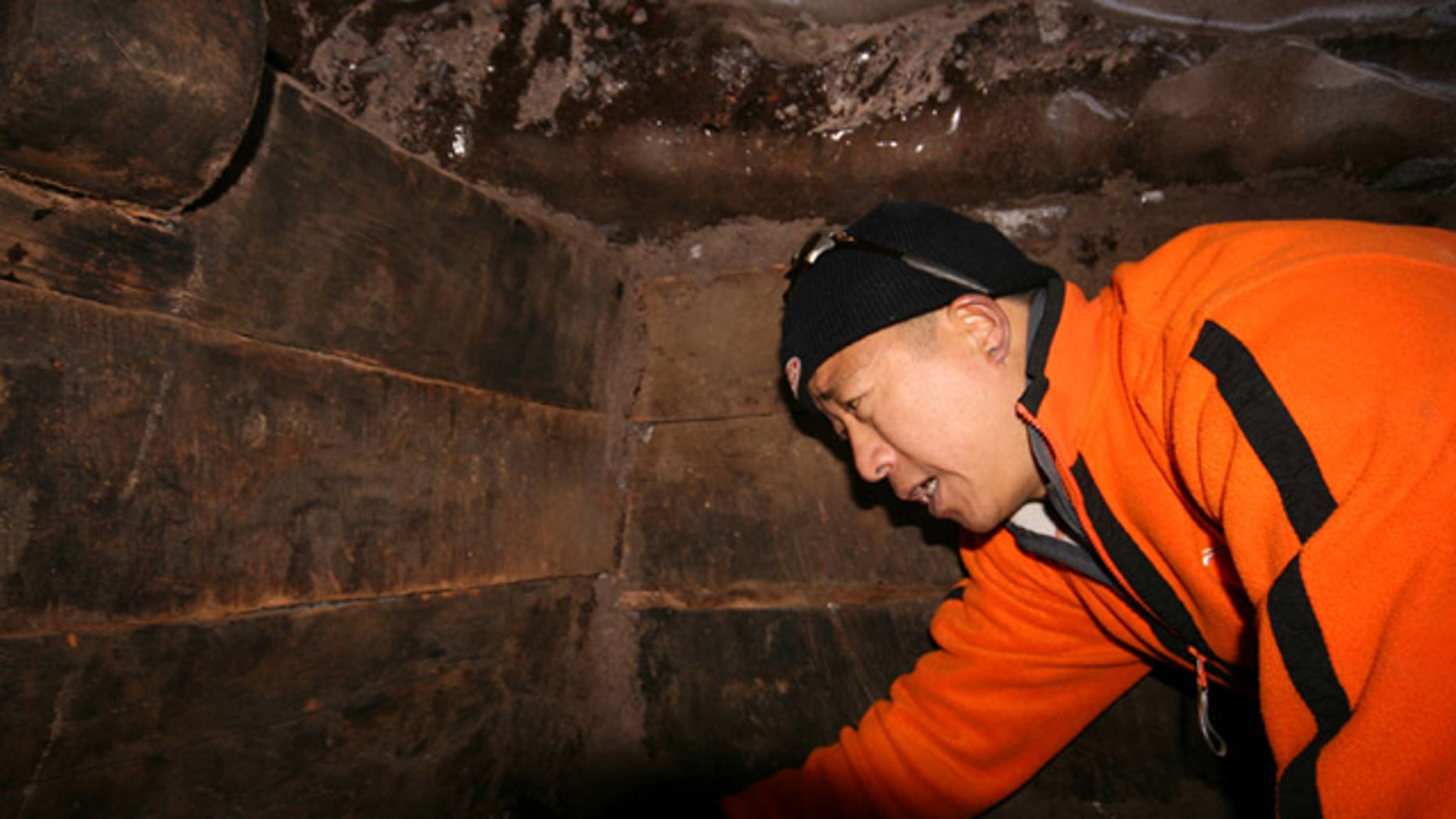 An explorer examines wooden beams inside what some are nearly certain is the remains of Noah's Ark.