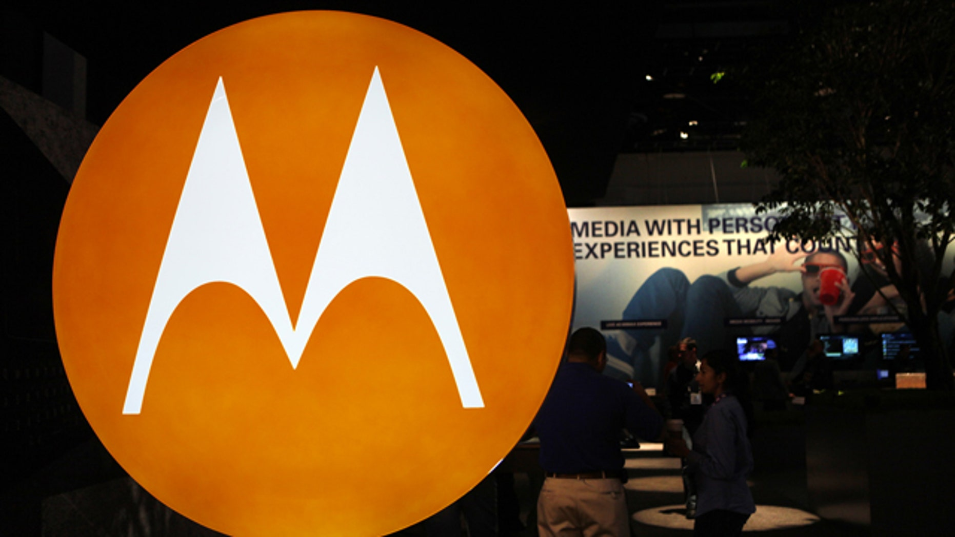 The Motorola logo is seen at the company's exhibit at the Consumer Electronics Show in Las Vegas. Motorola Inc. said Monday, July 19, 2010, that it is selling most of its wireless network division to Nokia Siemens Networks, a Finnish-German joint venture, for $1.2 billion as part of a planned breakup of the company.